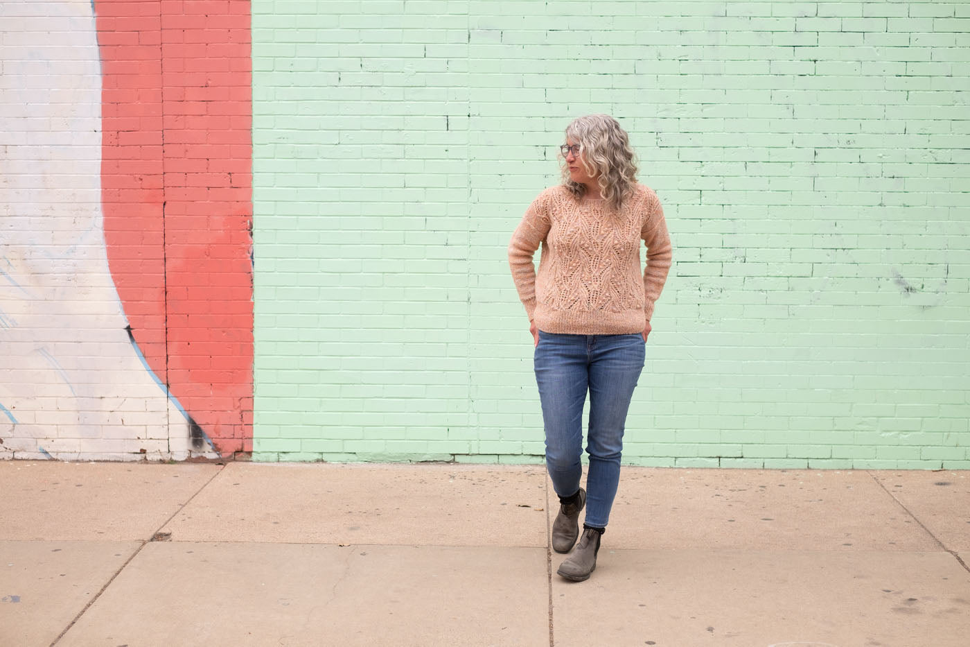 Jaime wears her peach hand-knit Atlantica pullover, standing in front of a colorfully painted mural wall in shades of mint, rose, and pale lavender.