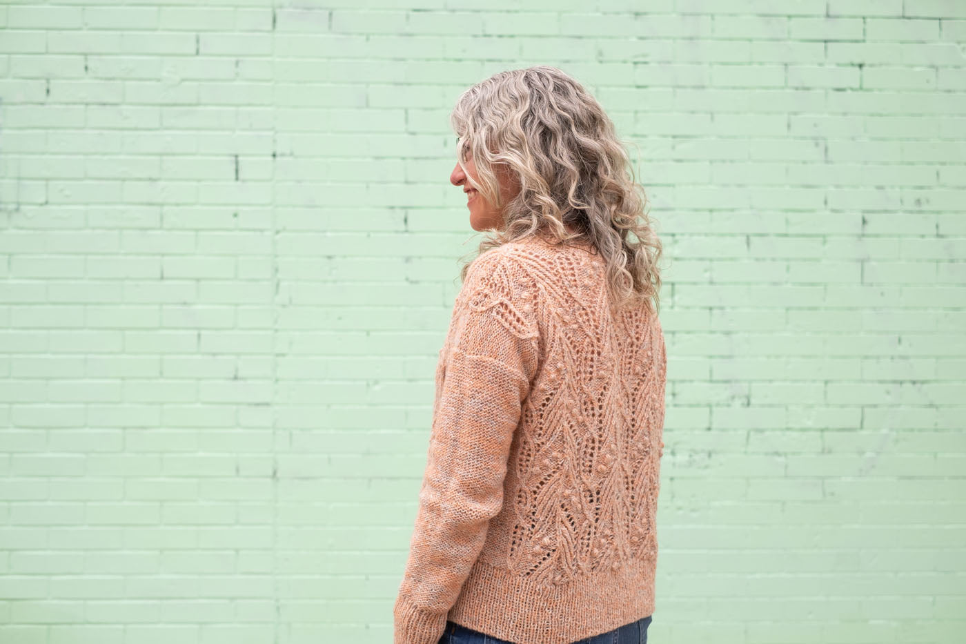 Jaime stands with her back to the camera, looking off to the side. The back of her hand-knit, peach, Icelandic wool sweater is just as intricately textures as the front.