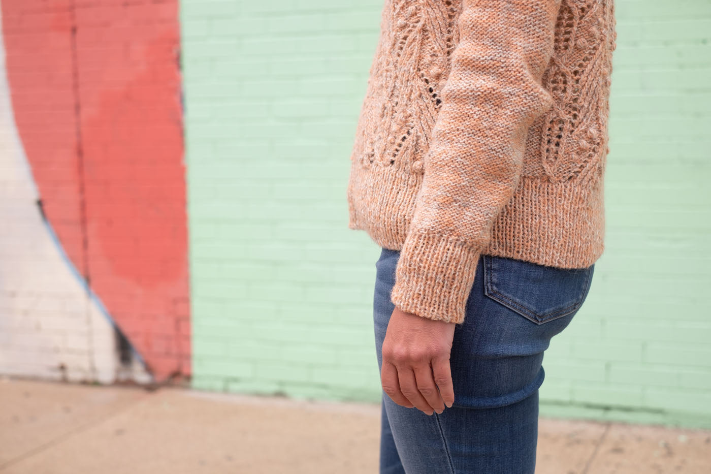 A detail shot showing the sleeve and hem of a peachy, textural handknit sweater.