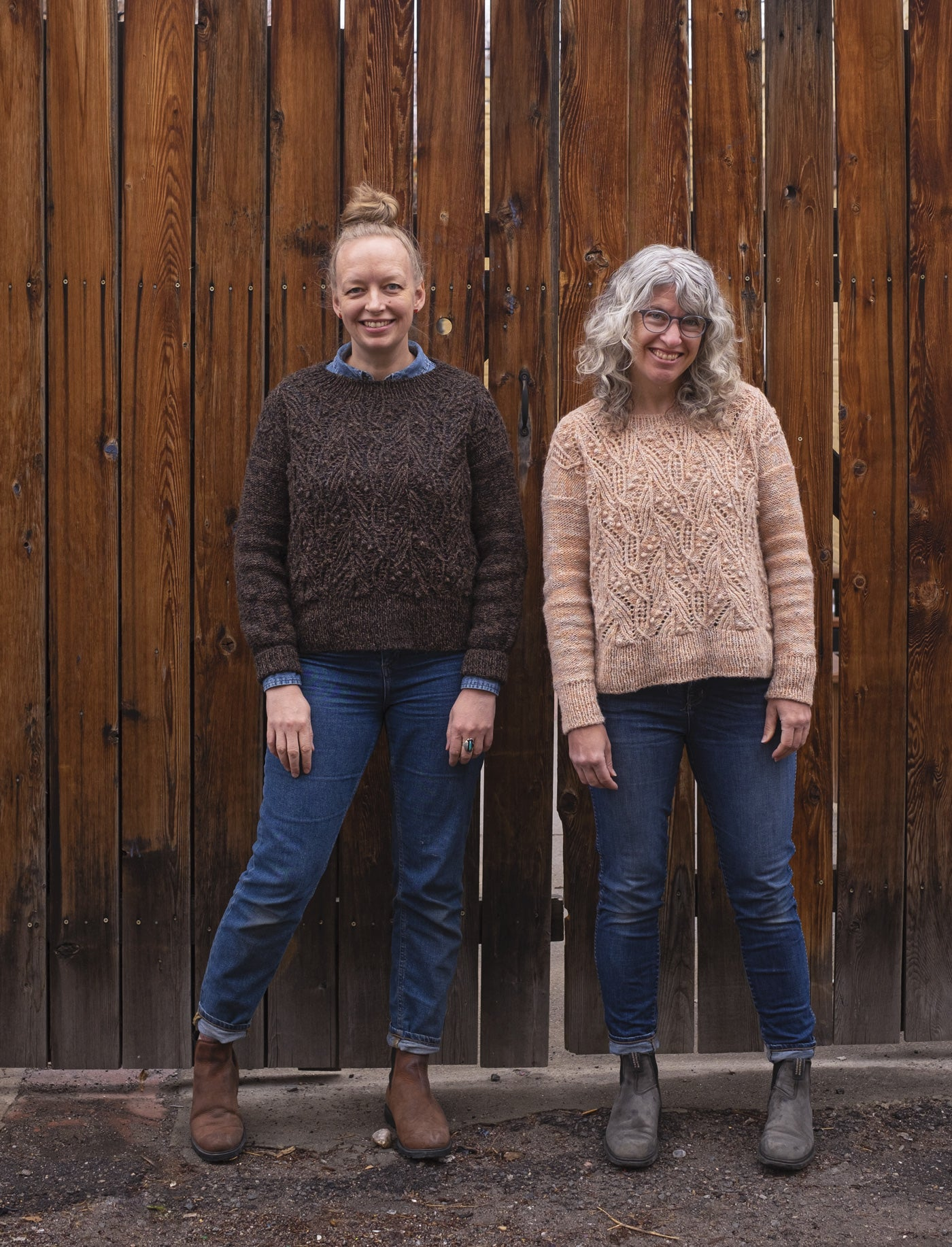 Amber and Jaime stand outside in front of a tall wooden fence on a rare damp day in Denver. They both wear their finished Atlantica pullovers: Amber's in a deep brown marl, and Jaime's in a pale peachy marl.