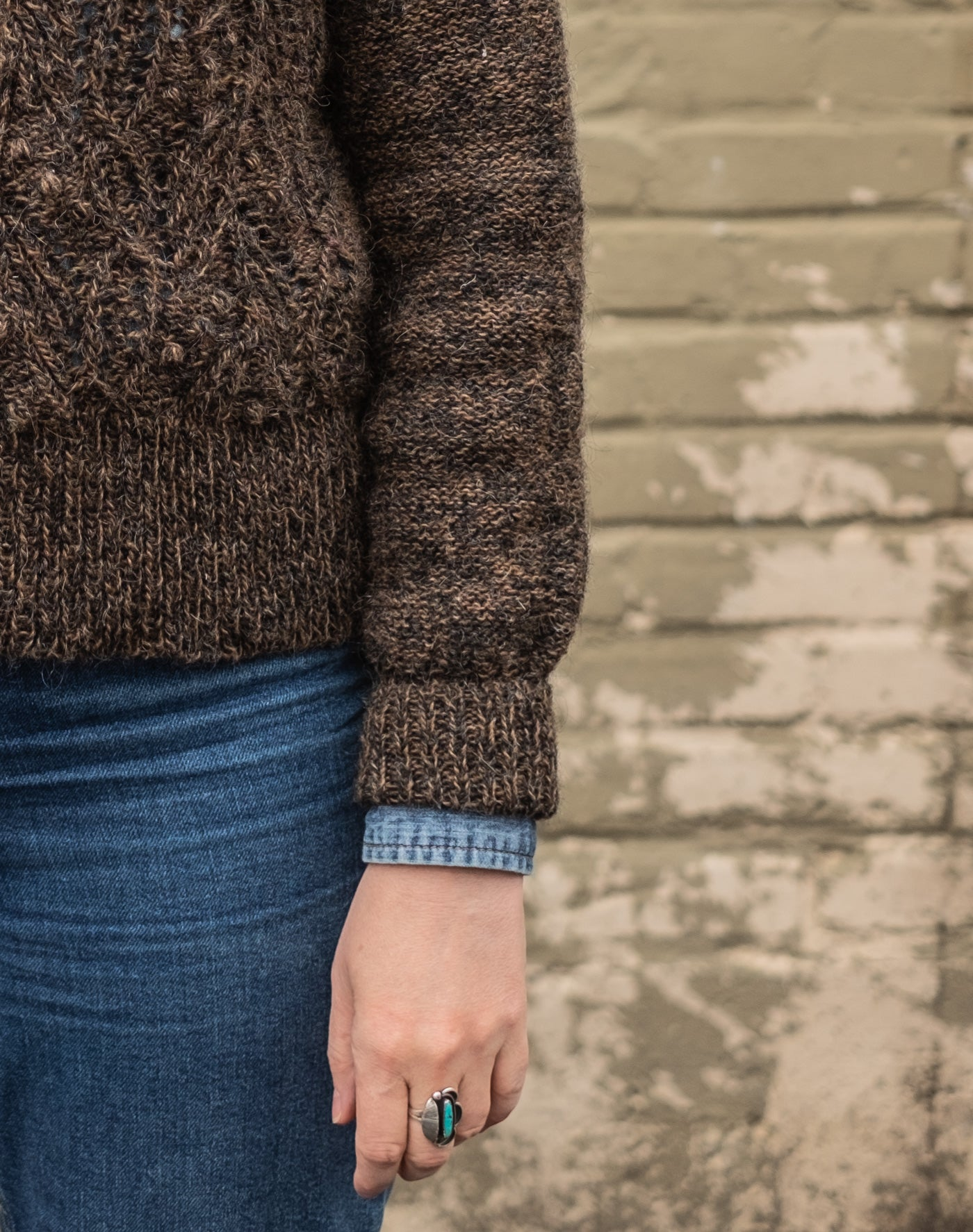 A close up of the bottom hem, sleeve and sleeve cuff of Amber's Atlantica pullover. The cuff is folded up and a bit of her denim button-up sleeve peeks out of the cuff.