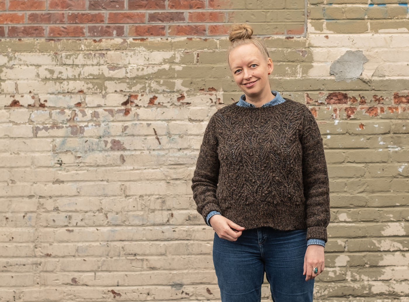 Amber stands smiling with her head tilted, wearing jeans, and a denim shirt under her hand knit Atlantic pullover. Her right hand gently grasps the bottom hem of her deep brown, textured sweater. Behind her is a brick wall painted in a patchwork of taupe hues.