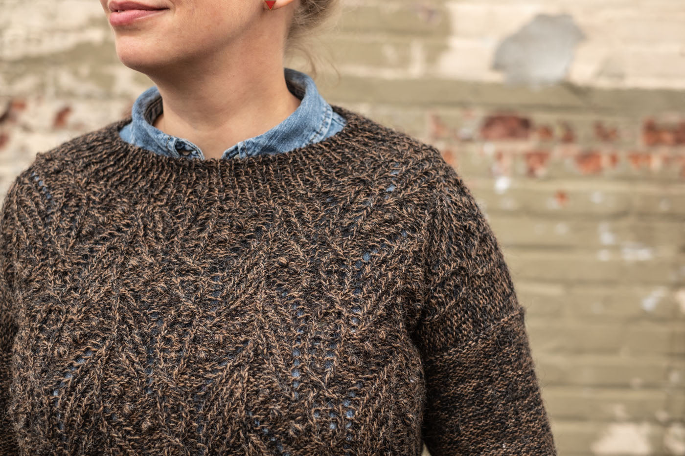 A close up of Amber's neckline on her brown Atlantica sweater. It fits similar to a crewneck, maybe slightly wider.