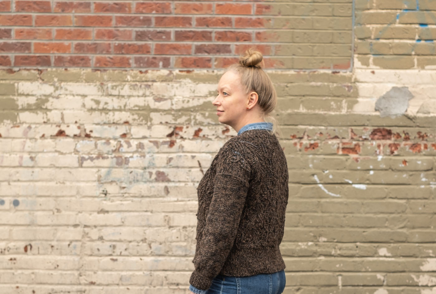 Amber stands in front of a taupe painted wall, looking off to the left. Her hair is in a topknot. Her brown hand knit sweater has long sleeves with a simple reverse stockinette stitch pattern, while the body of the sweater is intricately textures in a pattern of lace, cables and bobbles.