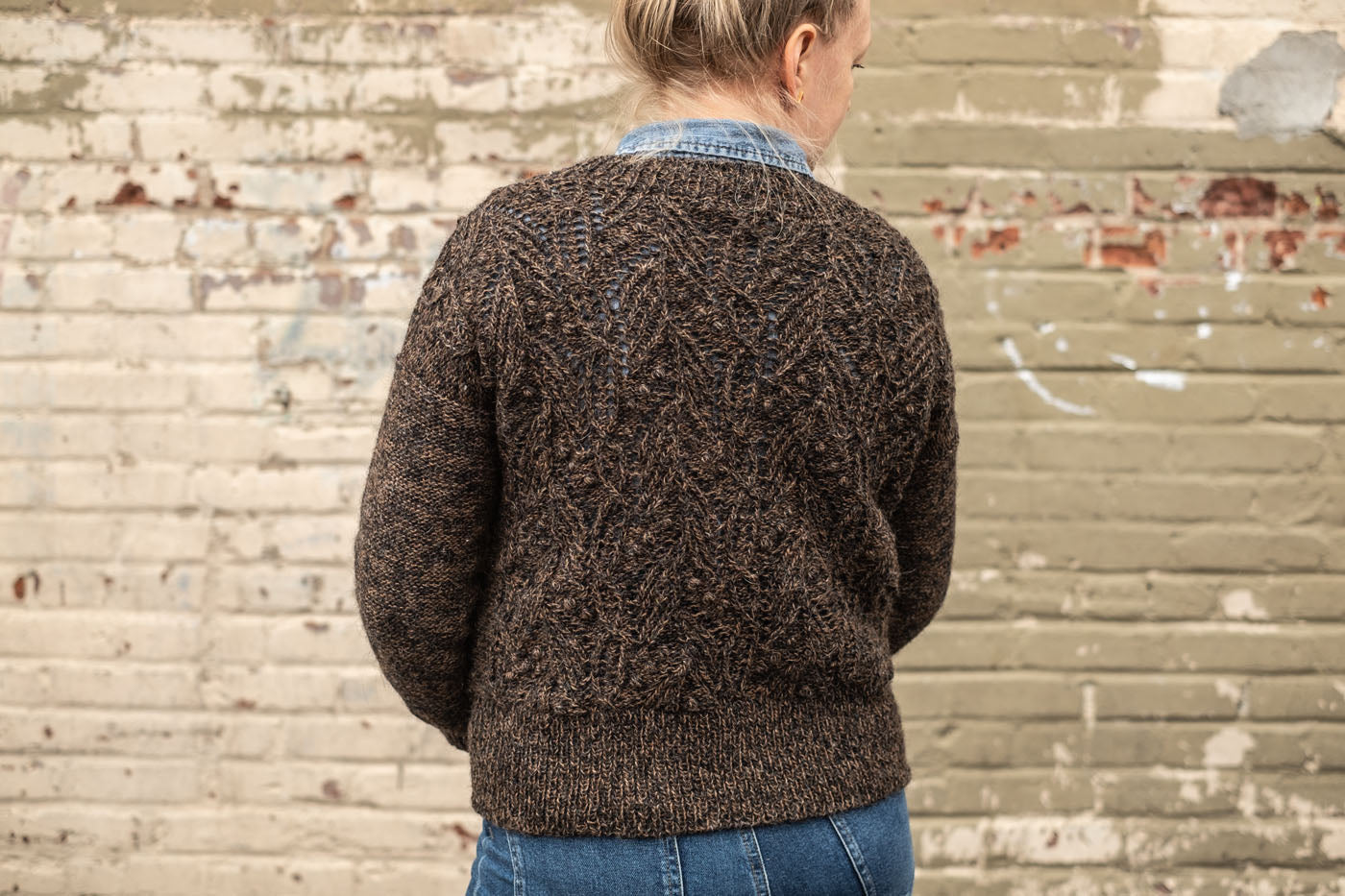 Amber is turned away, showing the back of her brown hand knit sweater is intricately textured with cables, lace and bobbles. Her blonde hair is up in a topknot and she wears blue jeans and an indigo button up under her hand-knit sweater. Behind her a painted brick wall is a patchwork of taupe hues.
