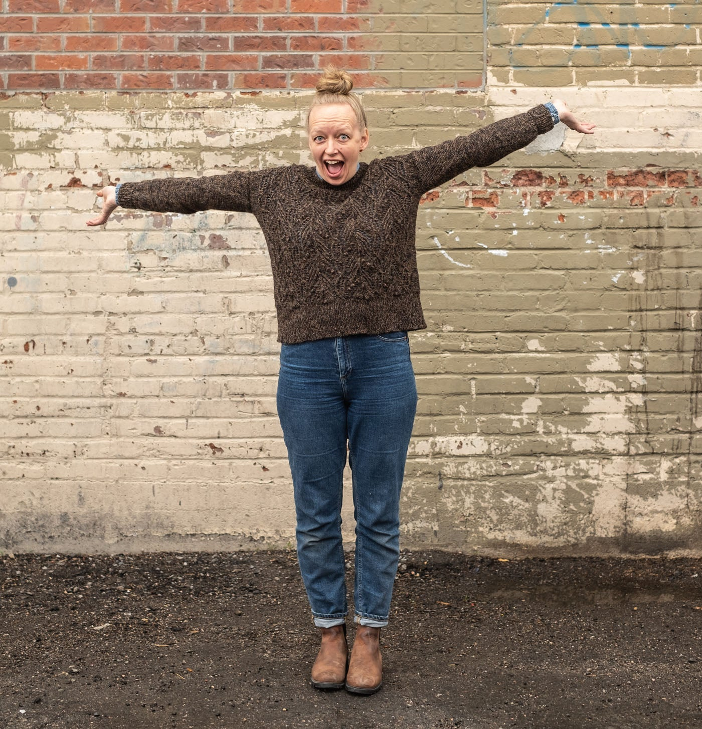 Amber has her arms flung wide with a giant goofy grin on her face.  She wears jeans, and brown leather boots along with her brown hand knit Atlantic pullover. Her blonde hair is in a top knot. Behind her is a brick wall painted in a patchwork of taupe hues.