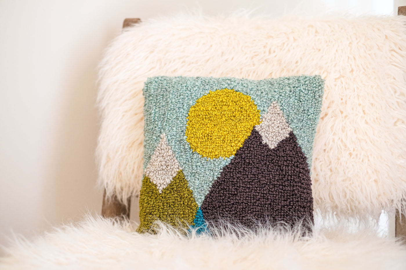 A punch needle pillow with geometric mountain and sun design. It is made in hues of green, blues, yellow, and grey, and is sitting on a plush sheepskin chair.