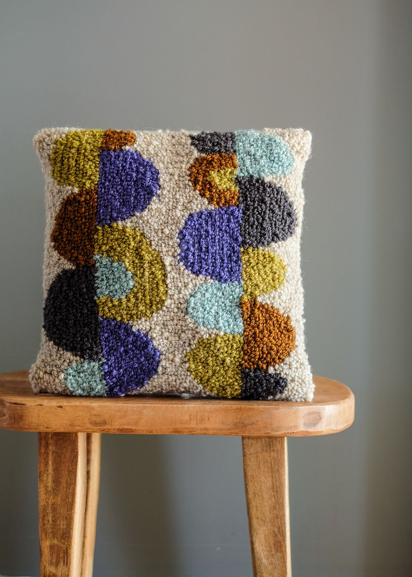 An abstract, modern punch needle pillow in hues of copper, grey, olive, pale turquoise and lavender.
