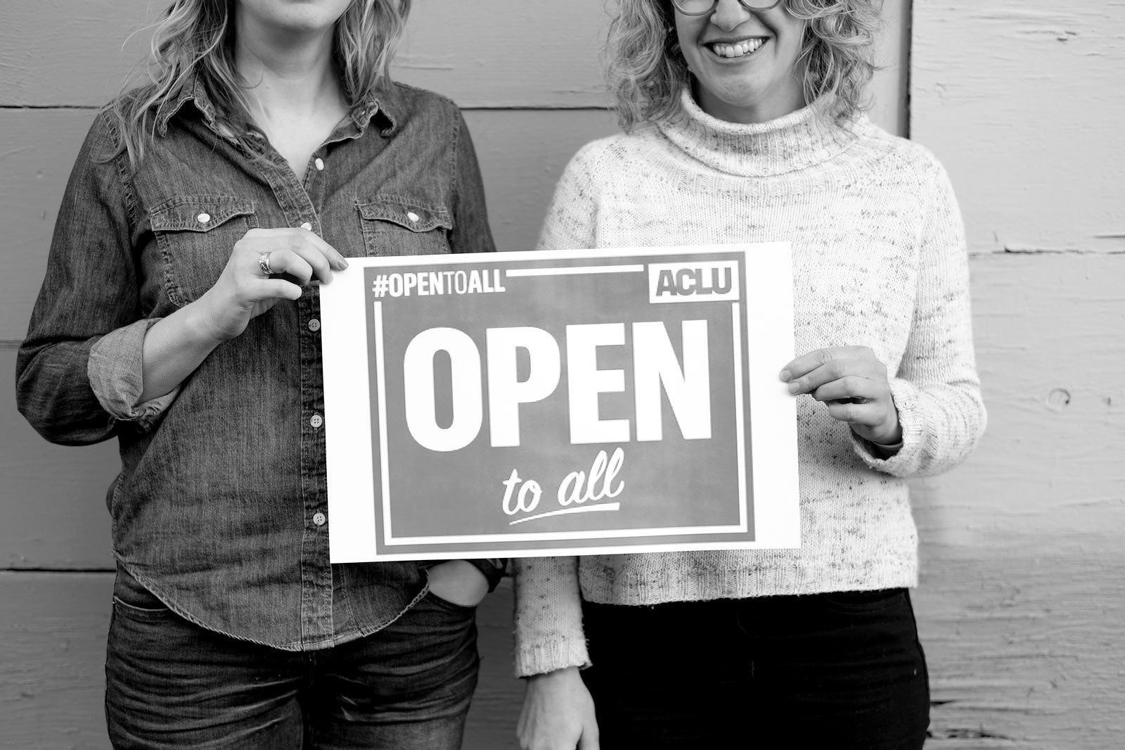 Jaime and Amber holding an ACLU Open to all Sign