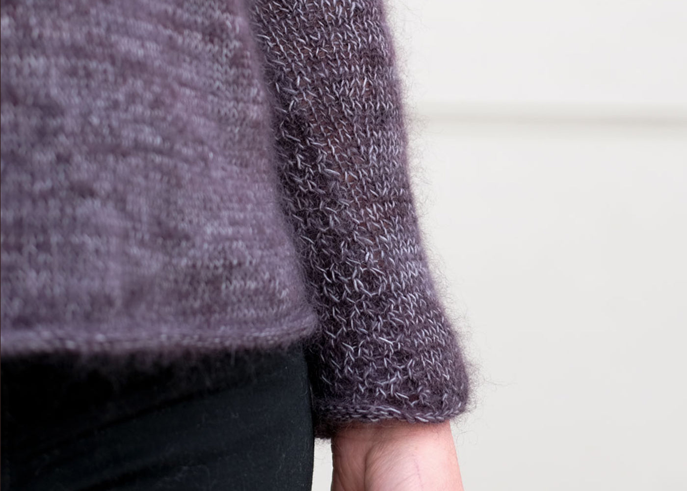 A close up of the hem and sleeve on a marled yarn soiree sweater