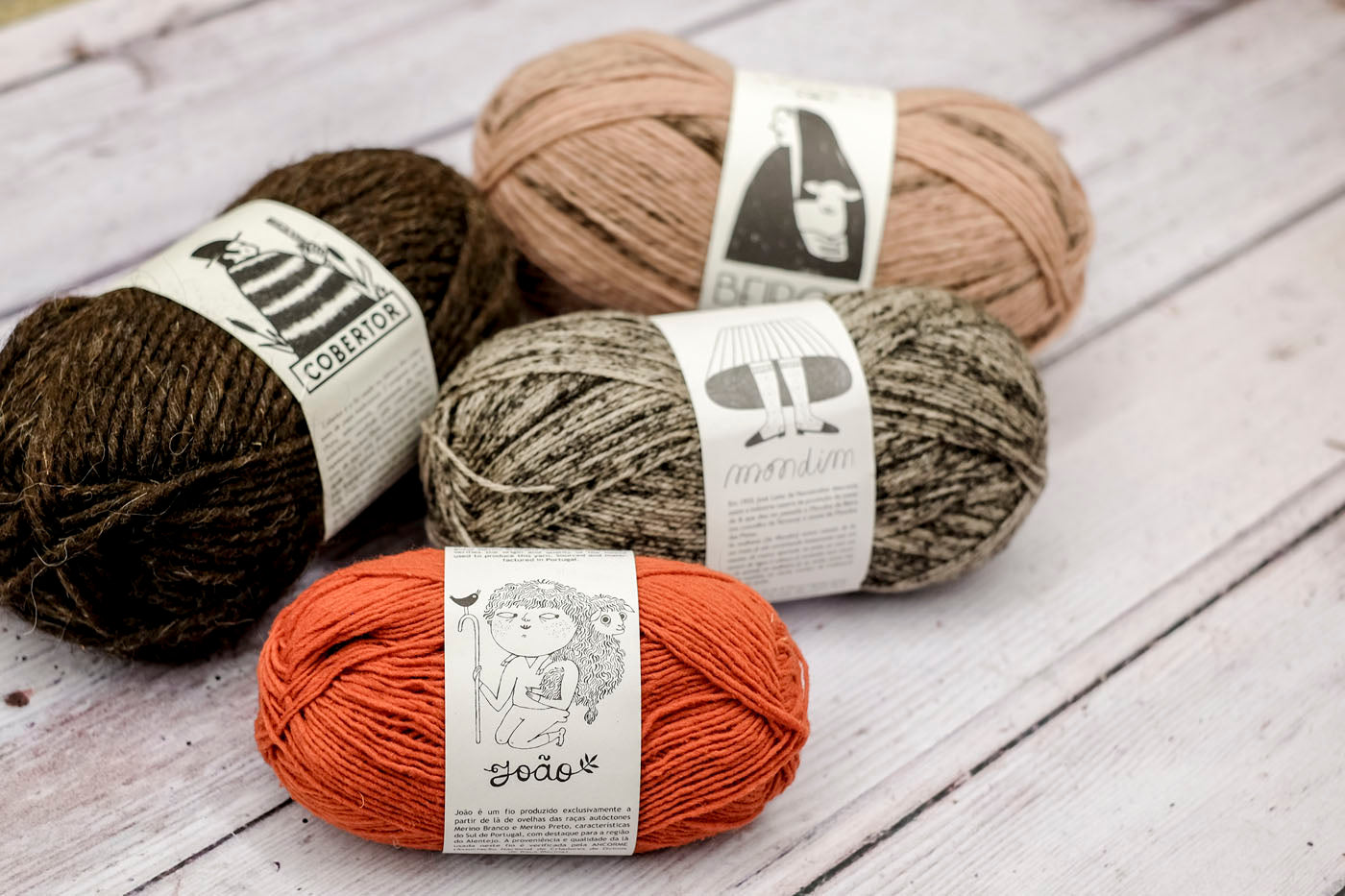 Four balls of Portuguese yarns, each of them has a different black and white illustrated label: shepherd woman holding a lamb, woman's socks, shepherd with blanket, and boy holding a sheep