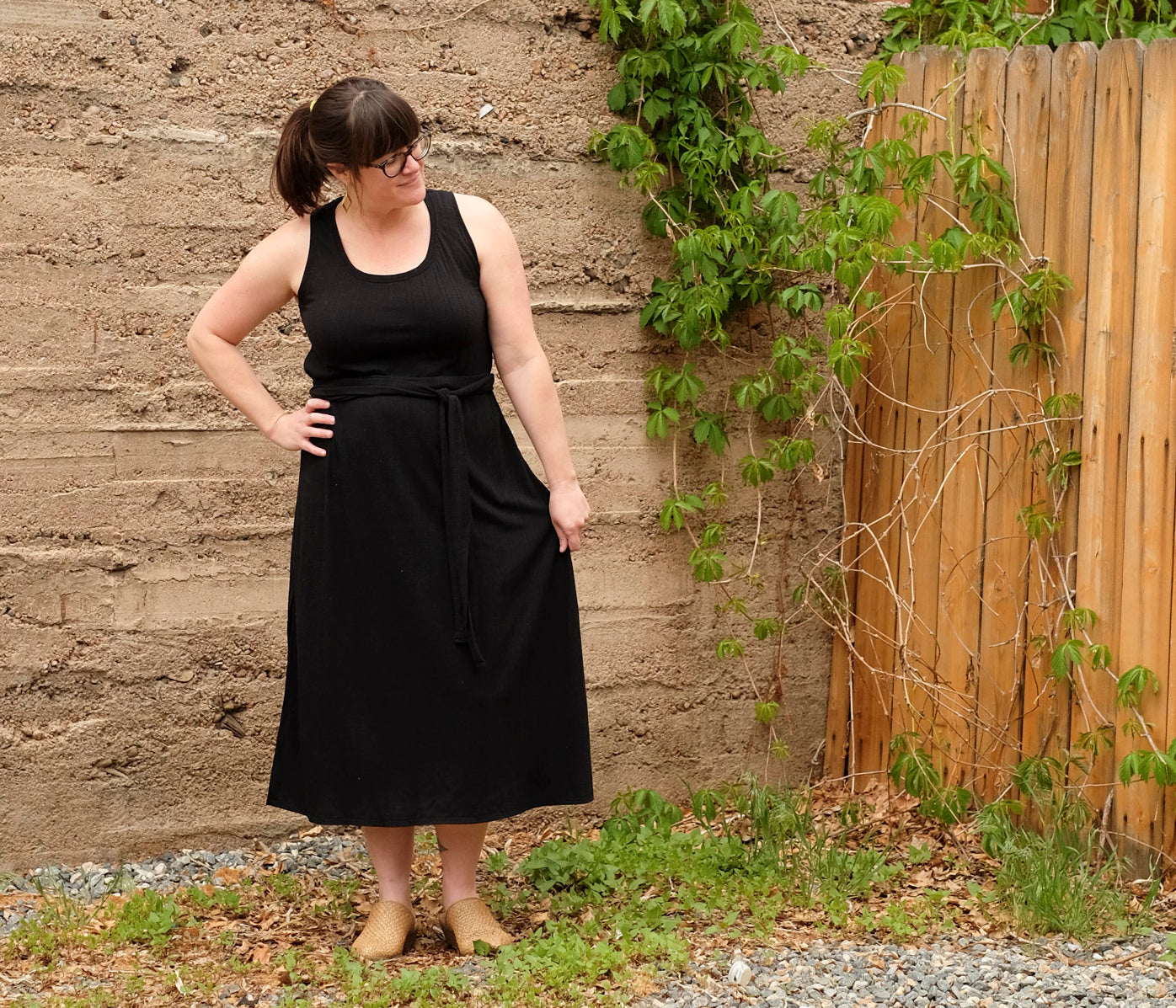 Amanda's standing in front of brick wall in handsewn maxi dress