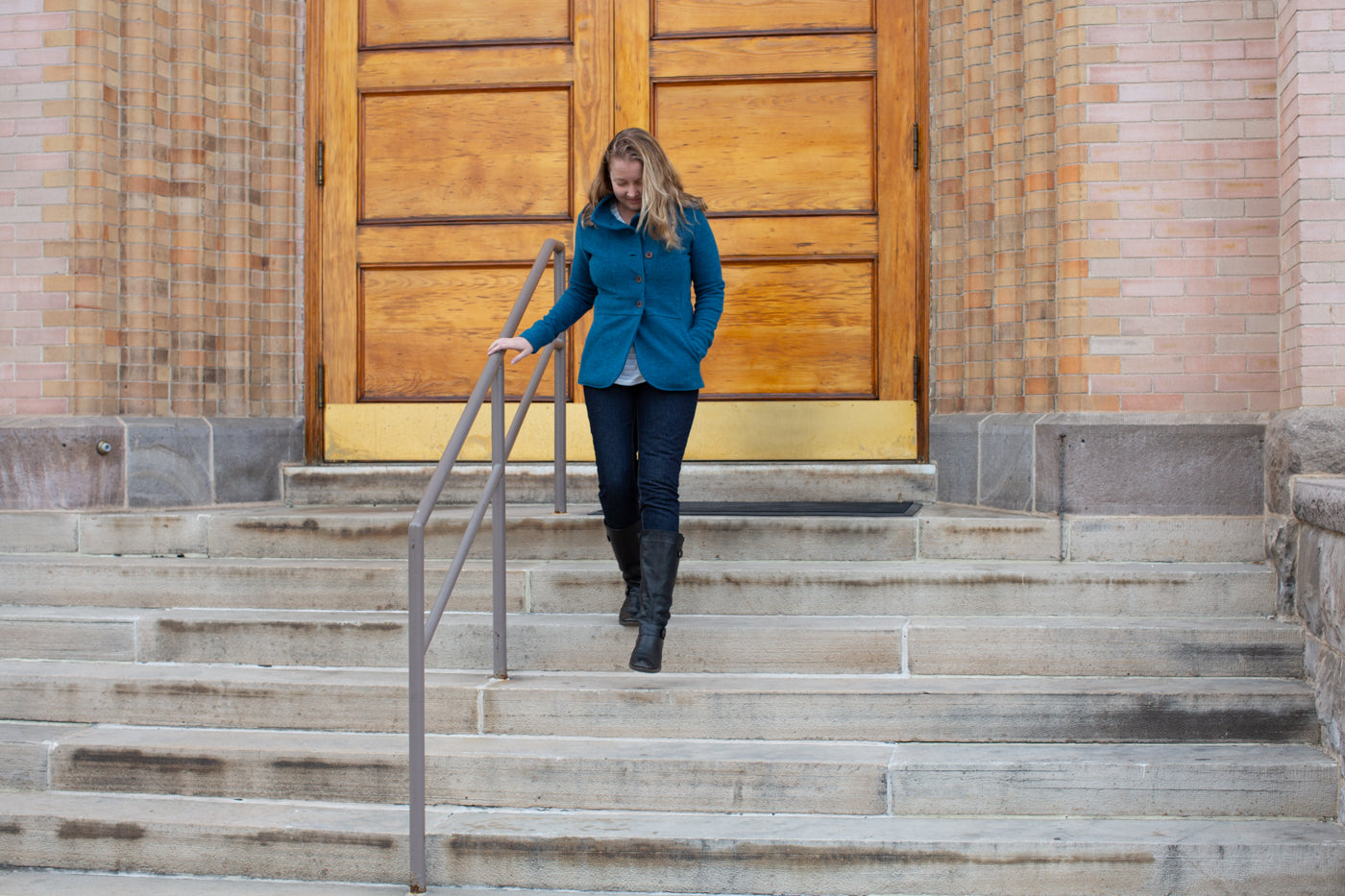 Danielle walking down stairs in front of a building with a large wood door.  Danielle is wearing denim jeans and an ocean blue peacoat.