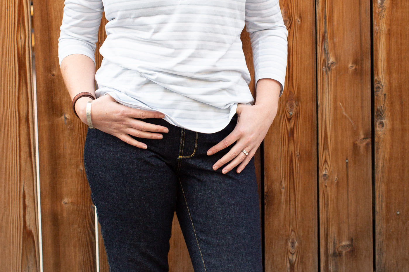 Photography close-up on a women wearing a white shirt and denim jeans with her hands in her pockets.