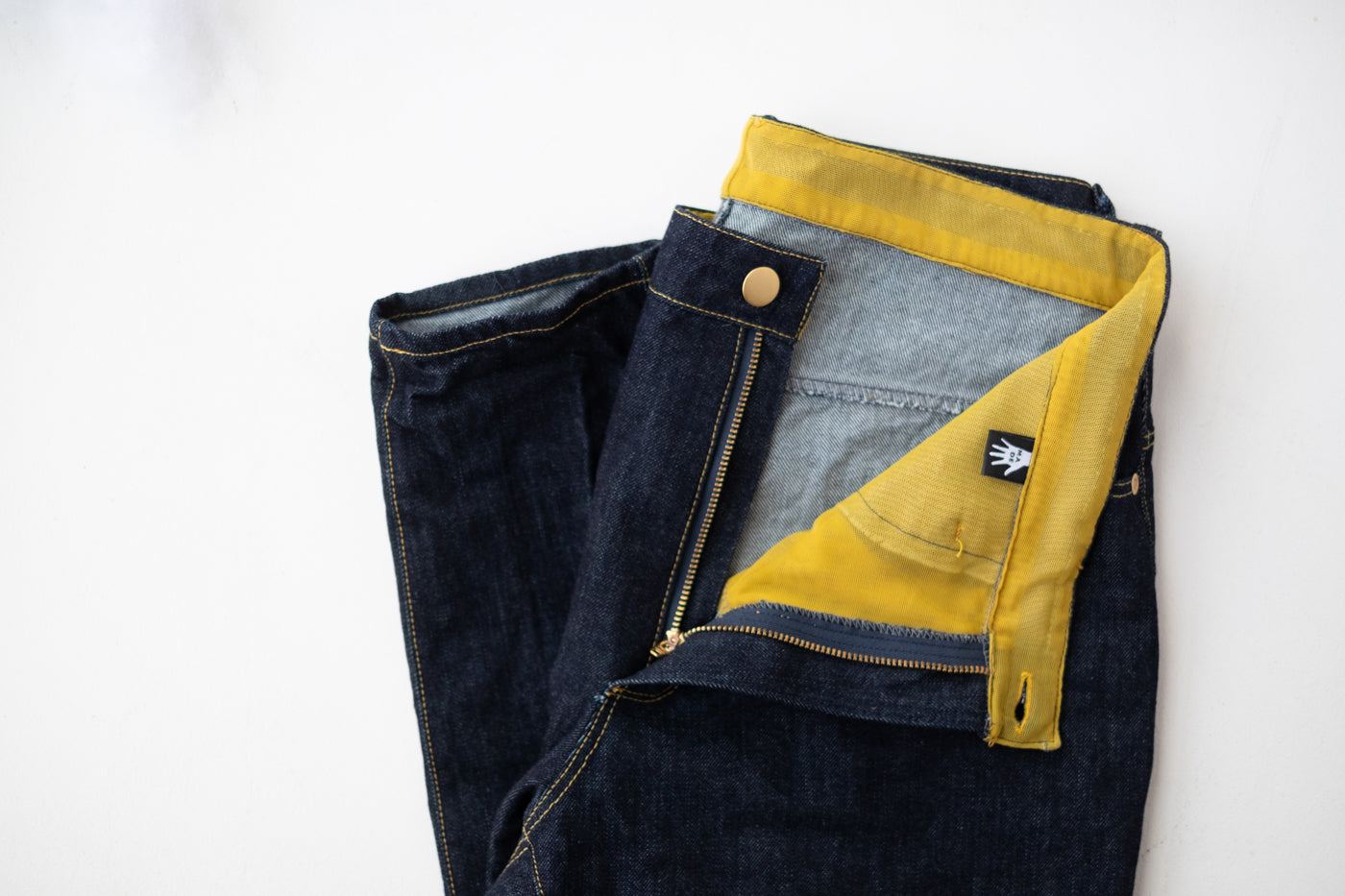 Demin jeans laying flat, folded on a white background.  The zipper is unzipped, folded back to show the yellow mesh lining with a custom label.