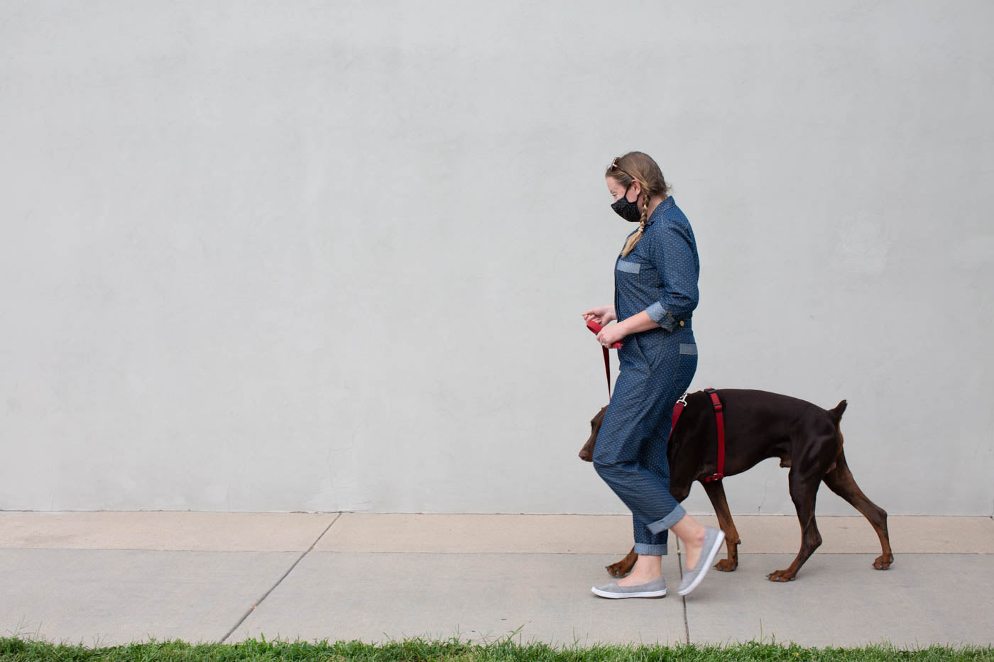 Women walking on a sidewalk past a grey wall wearing Thelma by Merchant & Mills in indigo dots with her brown dog walking beside her.