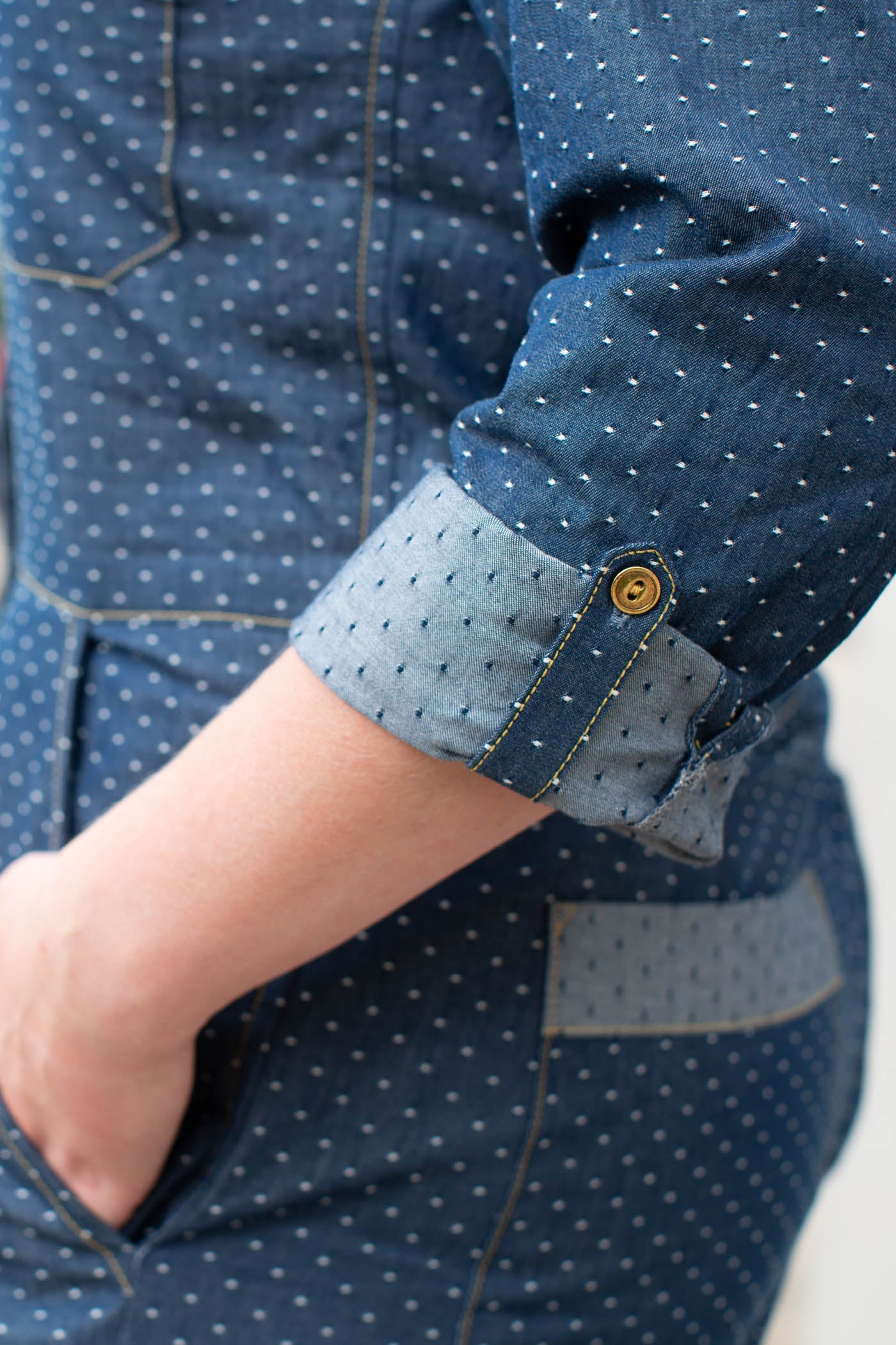 Detail photograph of Thelma by Merchant & Mills pattern with a cuff added to the pattern.  Fabric is indigo blue with white dots.