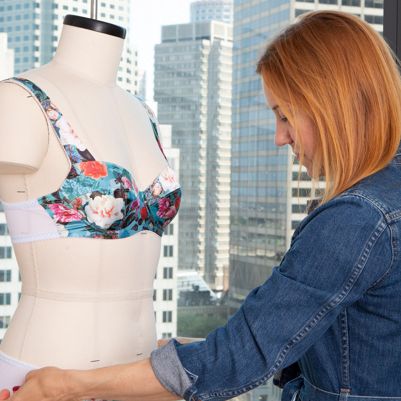 Side view of a Norma Loehr looking down and measuring a dressform, the dressform wears a bright, floral underwire bra. The background is a window onto a downtown cityscape.