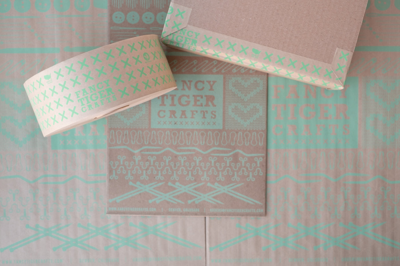 Eco friendly packaging in a flat lay looking down at the packaging.  One box and two shipping mailers with the words Fancy Tiger Crafts in a mint green.