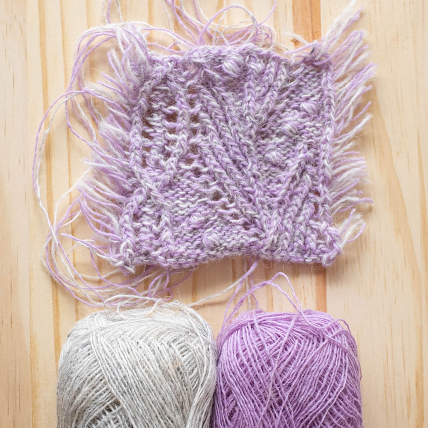 A knitted swatch for the Atlantica Pullover in a marl of two colors held together: Lavender and Light Ash Heather— lays on a background of light unfinished pine wood. The swatch features a delicate cabled lace. Two yarn balls in Lavender and Grey peek into the bottom of the picture.