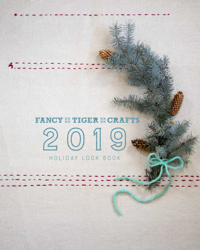 Cover of the Fancy Tiger Holiday Lookbook: A background of white canvas with red stitched lines, with a twig of holiday greenery around the title