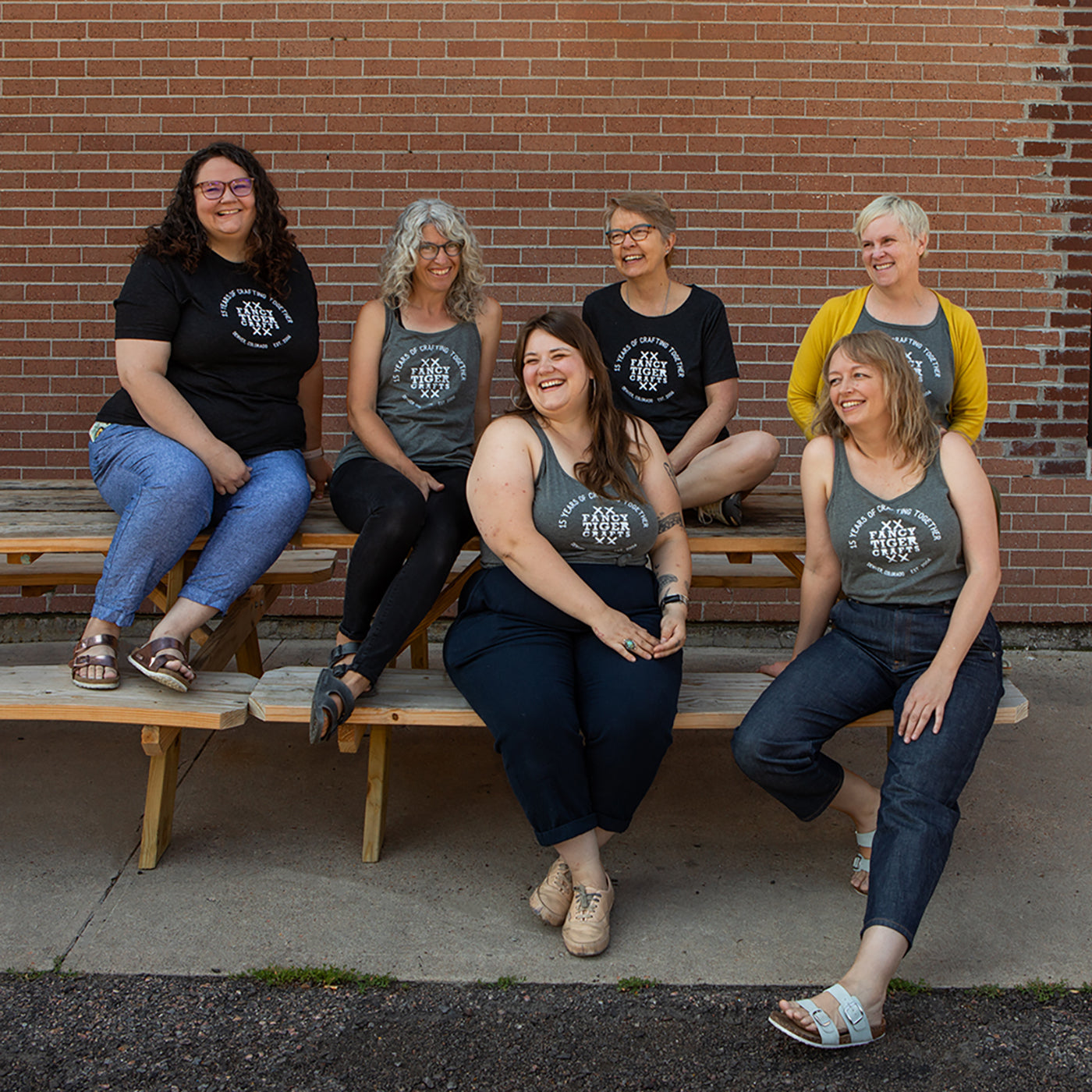 This is an image of women wearing Fancy Tiger Crafts shirts sitting on benches in front of a brick wall.