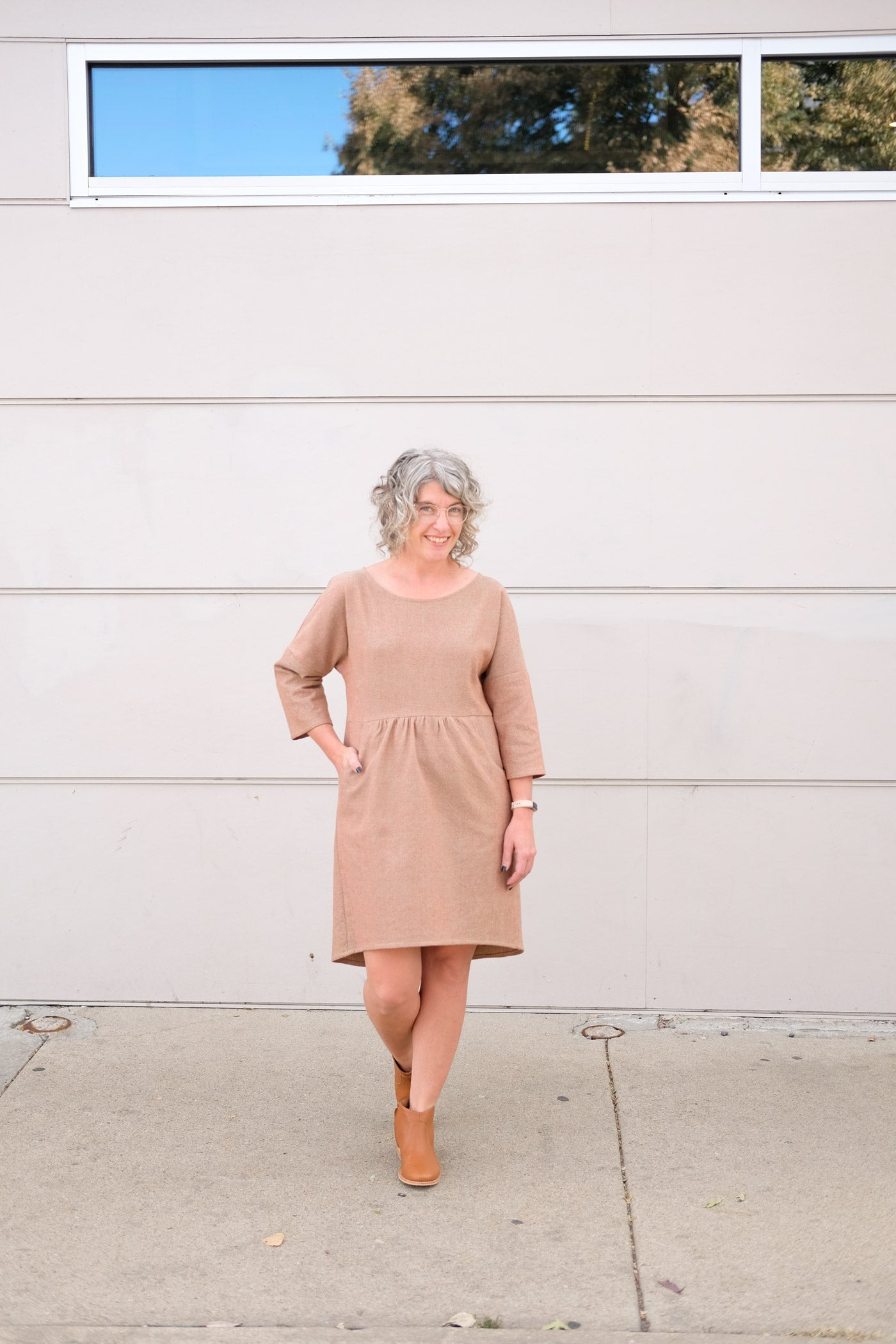 Woman in a pale brown, subtly textured dress. She stands outside in front of an off white wall. One hand is in a pocket, the dress is knee length, gathered at the waist, drop shoulder with 3/4 length sleeves and a scoop neckline.