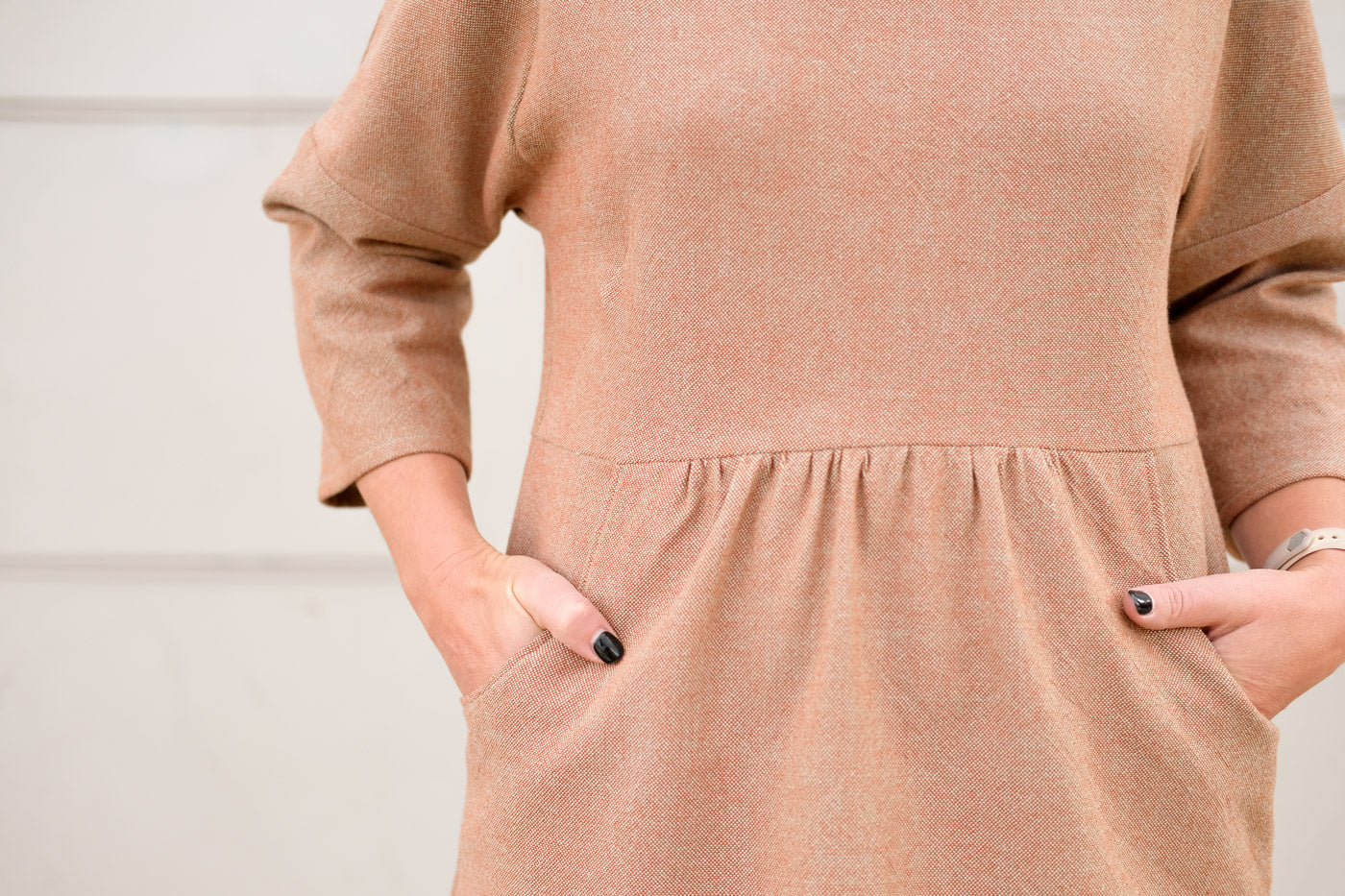 Detail of the waist and pockets of the Fen dress. It shows a close up of the subtly textured, plain weave fabric, and Jaime's hands in the waist pockets.