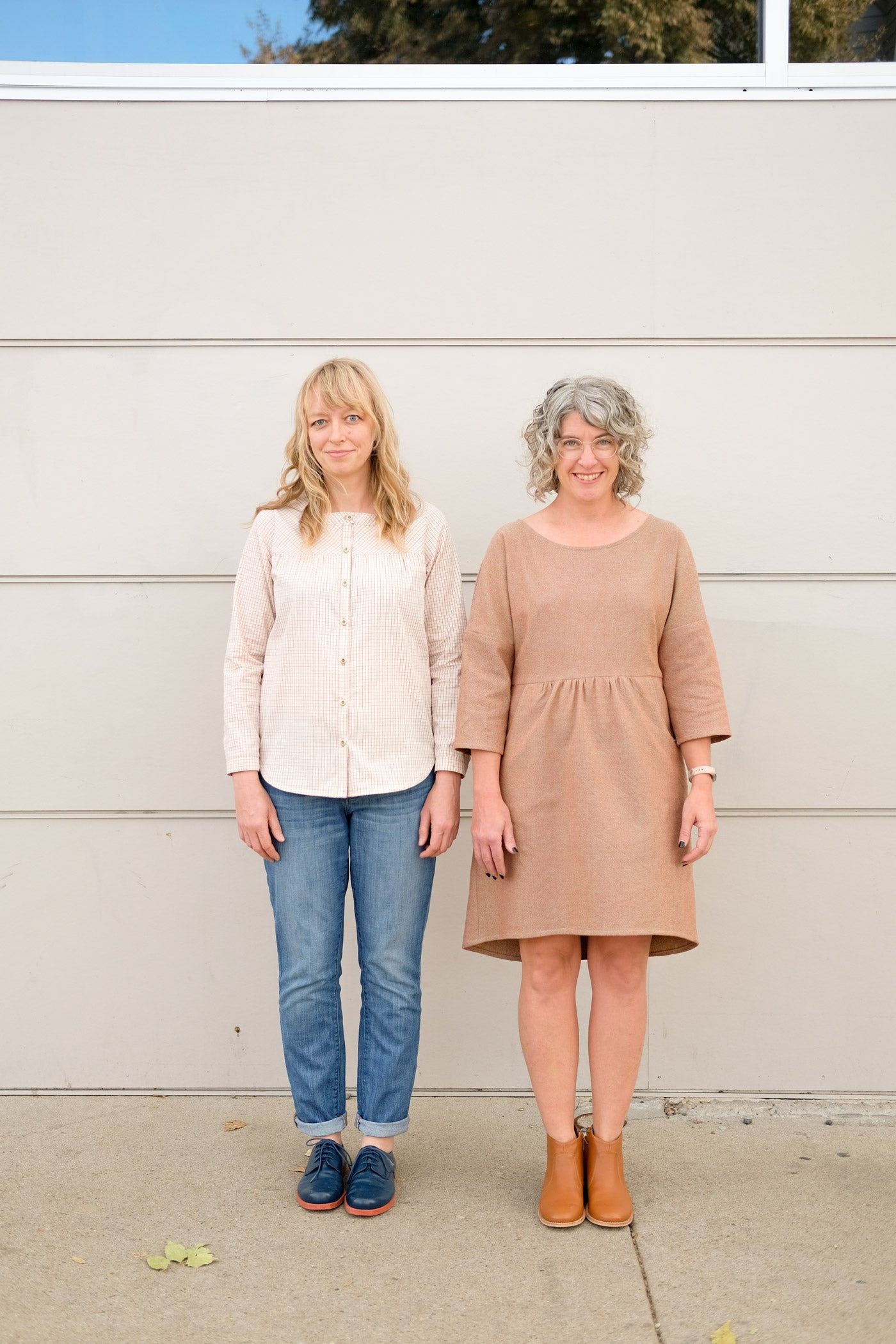 Two women standing in front of an off-white wall outside. One wears jeans and a light plaid button up shirt, and the other wears a light brownish knee-length dress with 3/4 sleeves and a gathered waist with pockets.