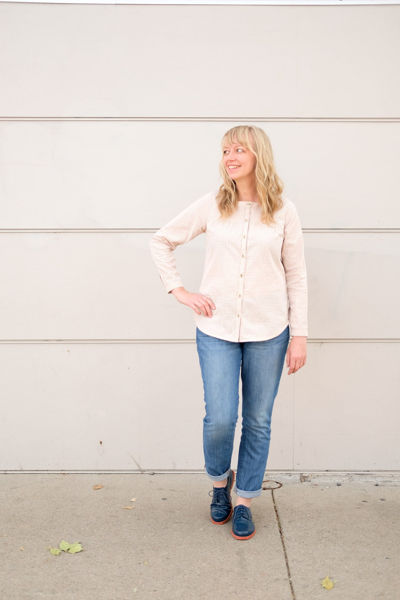 Woman standing in front of an off white wall in jeans and a very pale peach button up shirt. She smiles and looks off to the left with one hand on her hip.