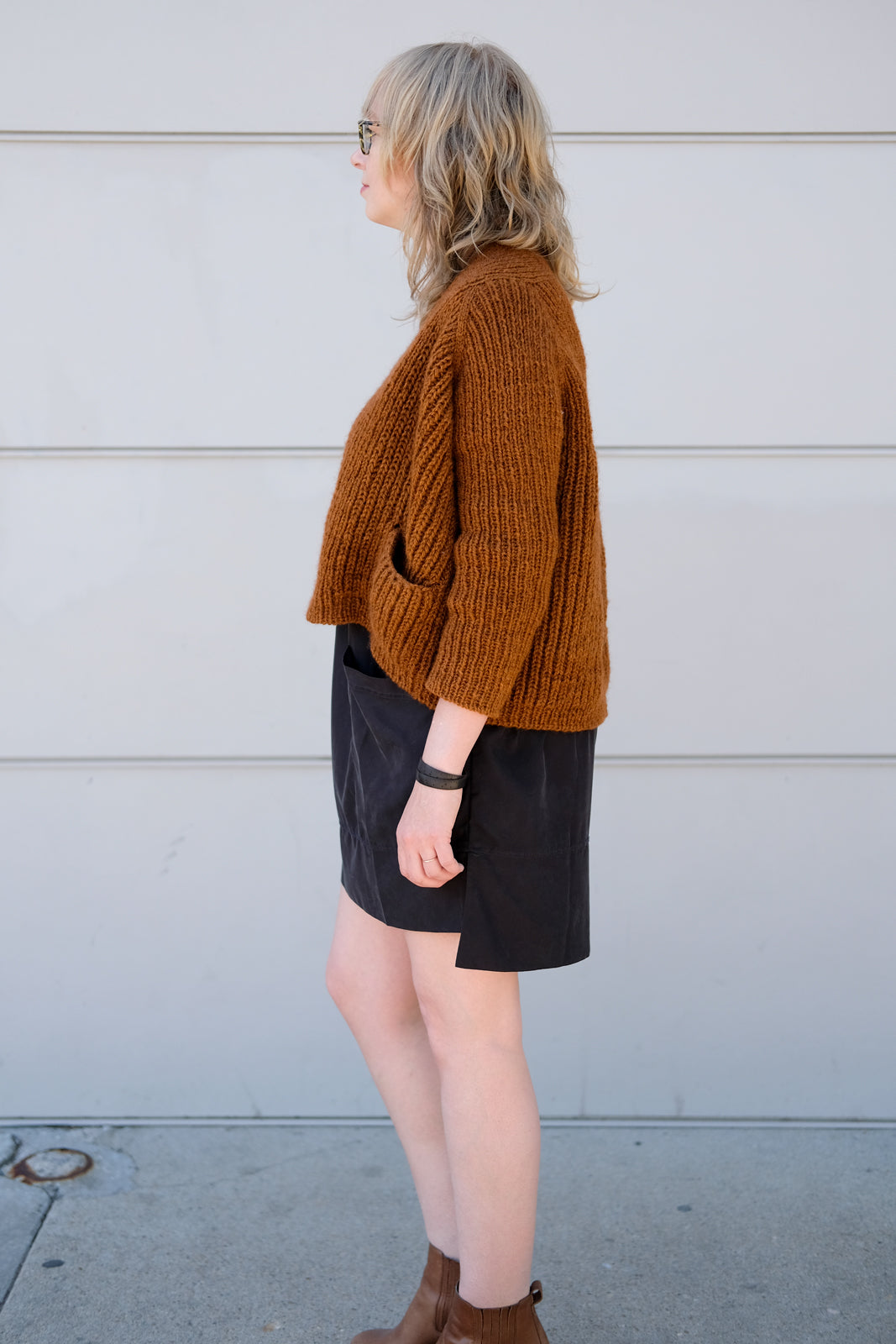 Side view of this boxy copper colored sweater