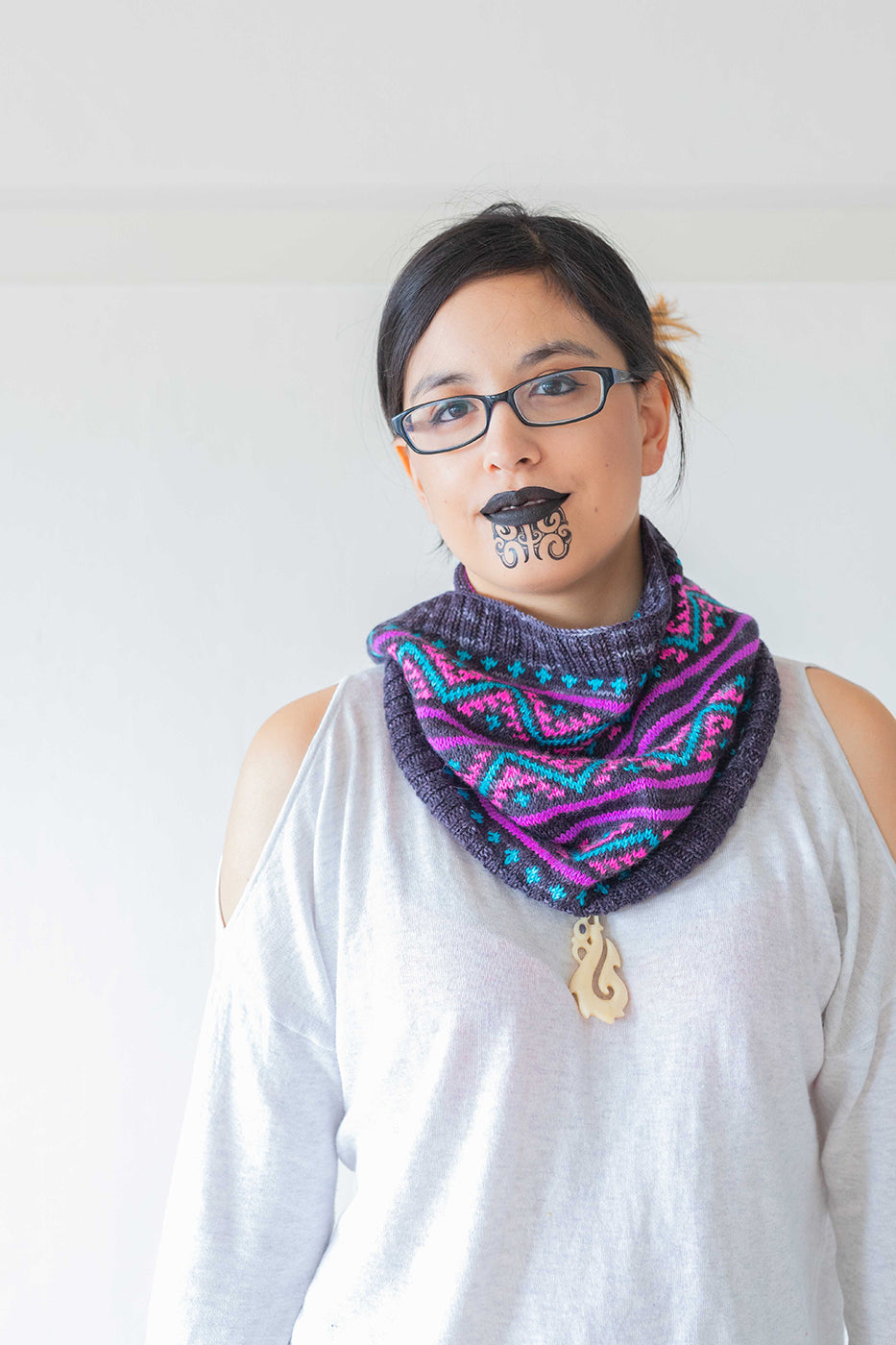 Photograph of women standing looking straight faced at the camera.  Women is wearing glasses and has face tribal painting on her chin.  Women is wearing a long sleeved white top with a colorful knit scarf in purple, blue and pink.