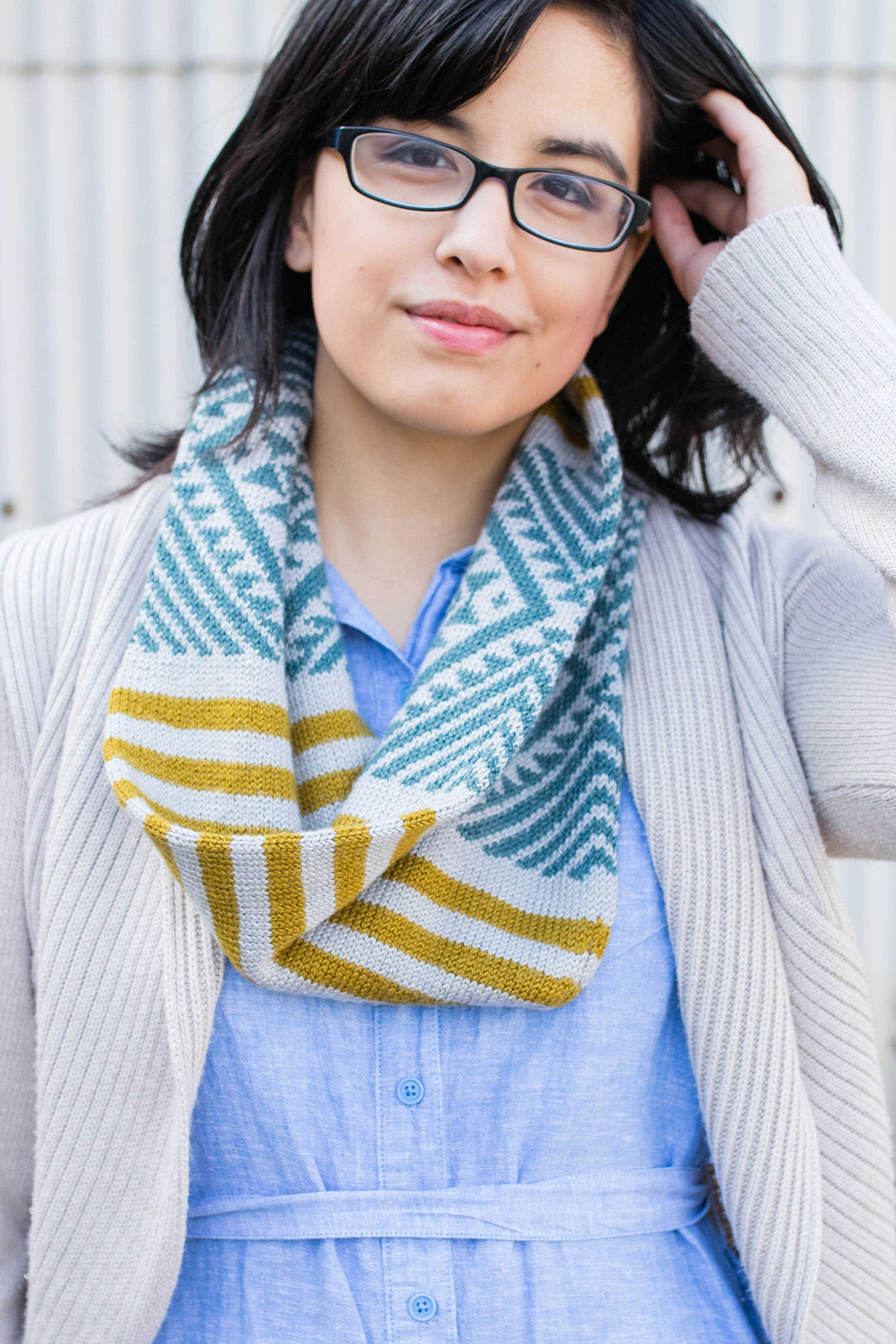 Photograph of a women wearing a light blue top, oatmeal knitted sweater with a colorful scarf in dark yellow and teal.  Women is facing the camera with a slight smile and has her left hand in her hair.