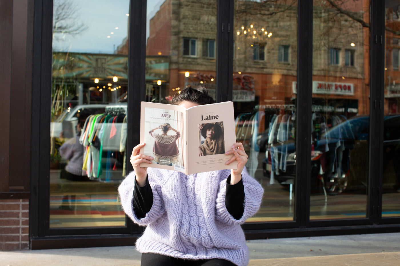 Women sitting on a bench.  Women is wearing a pale lavender knitted cable sweater, holding up a Laine magazine in front of her face.