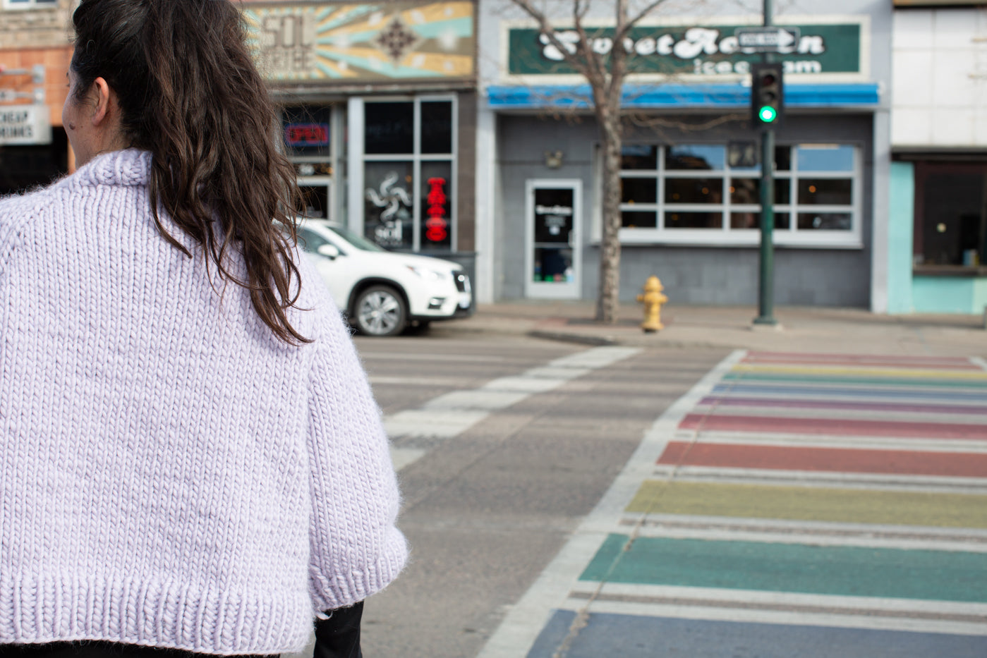 Women wearing a pale lavender cable knit sweater, facing a cross walk.  Photograph is the back of the sweater with the women looking off left with a city street in front of her with a rainbow crosswalk.