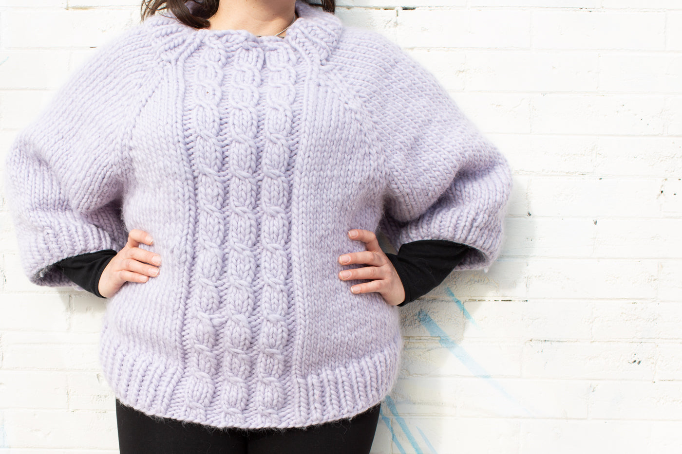 Women wearing pale lavender cable knit sweater, with her hands on her hips and the photograph is taken close up to show the sweater only.