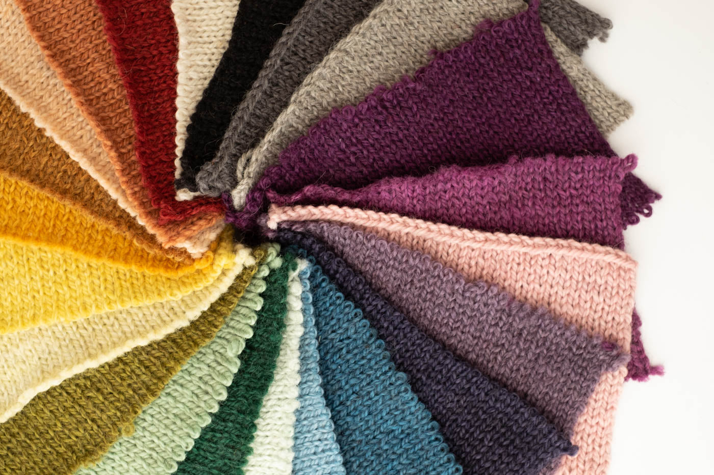 Knitted rectangular color swatches in the colors of the rainbow all in a circle.  Up close photograph of the colors.
