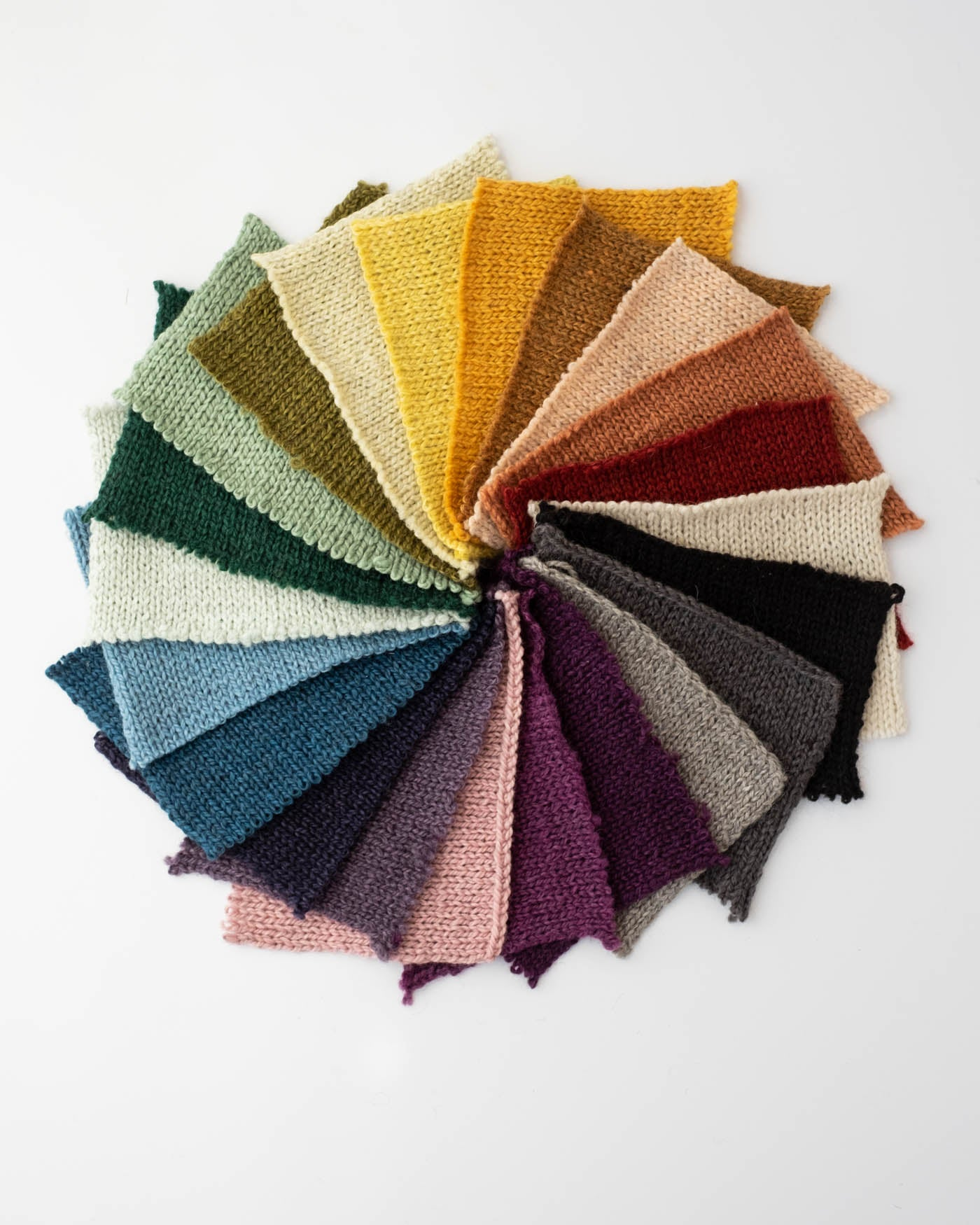 Rectangular knit swatches in the color of the rainbow in a circle to show all 22 colors.