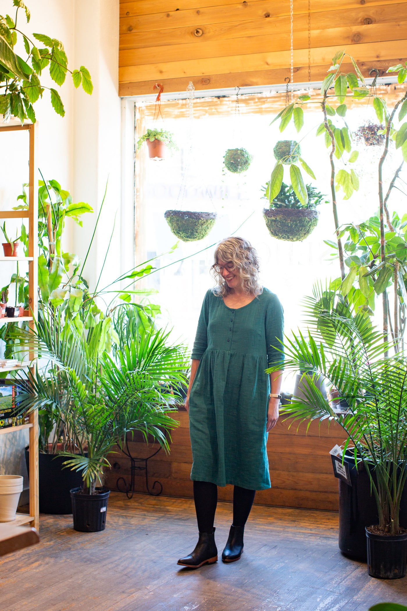 Jaime standing in front of a large window in a plant shop with sun filtering in.  Jaime is wearing a spruce linen dress, black leggings and shoes.  Jaime is surrounded by green plants.