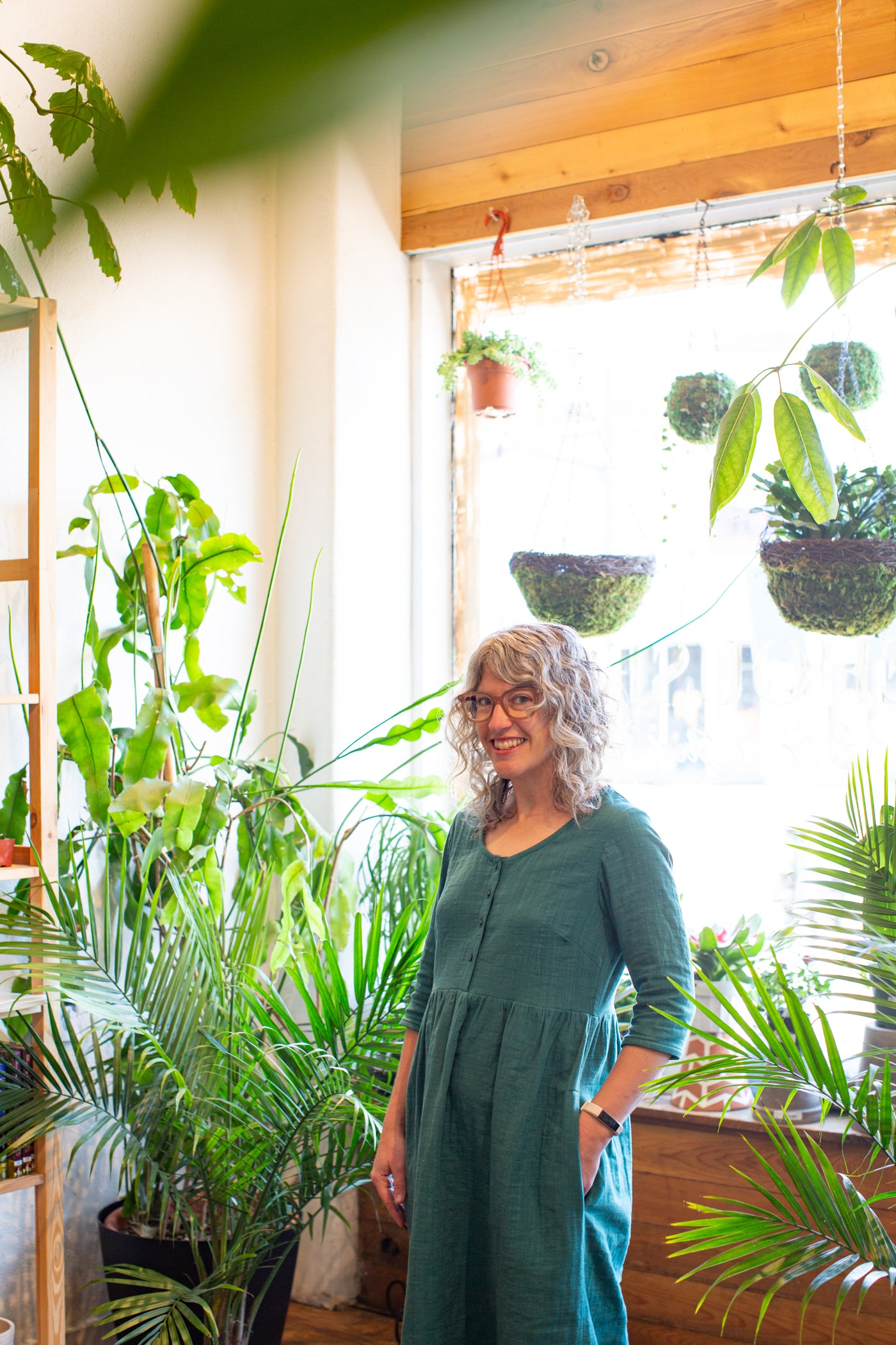 Jaime wearing a Japanese Cotton Slub Double Gauze dress in the Spruce color.  Jaime is in a plant shop surrounded by green plants, in front of a large window.  Photograph is knees up with Jaime standing sideways towards the camera, with her left shoulder towards the camera, with her left hand in her pocket.