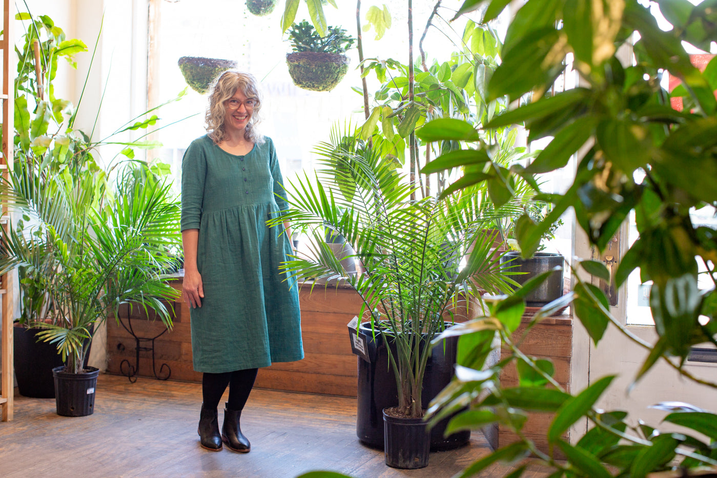 Jaime standing in front of a large window in a plant shop with sun filtering in.  Jaime is wearing a spruce linen dress, black leggings and shoes.  Jaime is surrounded by green plants