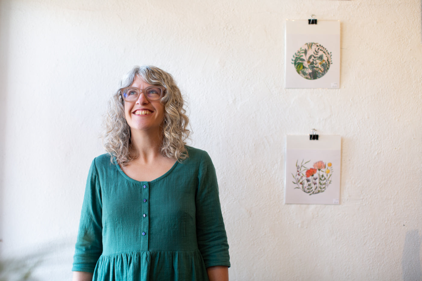 Jaime wearing a Japanese Cotton Slub Double Gauze dress in the Spruce Color.  Jaime is facing the camera, smiling, lookin up, in front of a white wall with two images hanging on the wall behind her.