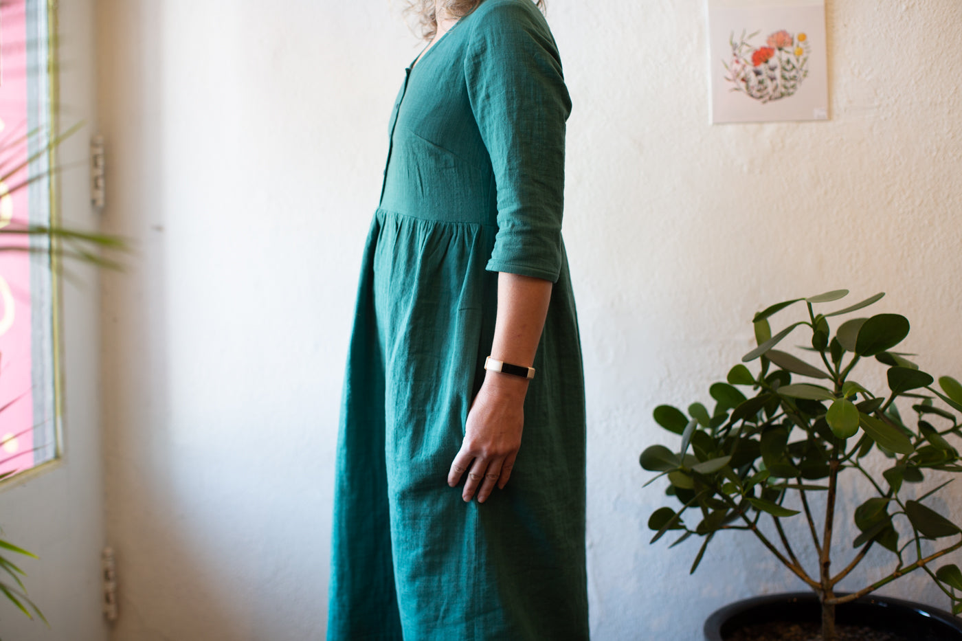 Jaime is wearing a spruce linen dress.  Facing towards a store front door with glass.  Photograph is focusing on showing the sleeve and pocket detail.  Photograph is from the side.