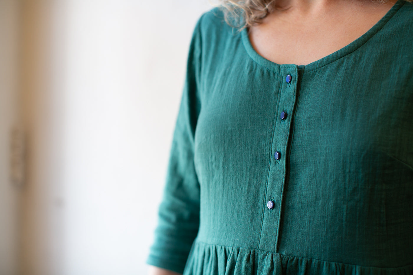 Photograph showing geometric shape of Atelier Brunette buttons on a Spruce colored double gauze dress.  Up close photograph of buttons.