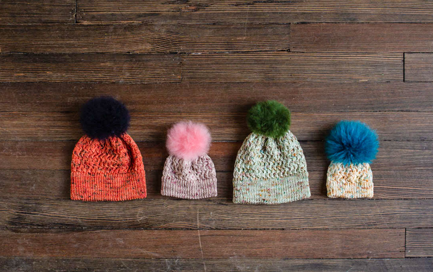 Four hand knit hats lay in a row on a dark wood background. They are made in a variety of sizes from newborn to adult, and a variety of hues of speckled, hand-dyed yarn. Each one is topped with a soft, alpaca fur pompom in a coordinating or contrasting color: a large hat in fiery orange with deep navy speckles is topped with a dark navy pompom; a small pink and grey hat is topped with a pale pink pompom; a sage green hat is topped with an olive green pompom; a tiny newborn hat in speckles of beige and turquoise is topped with a vibrant turquoise pompom.