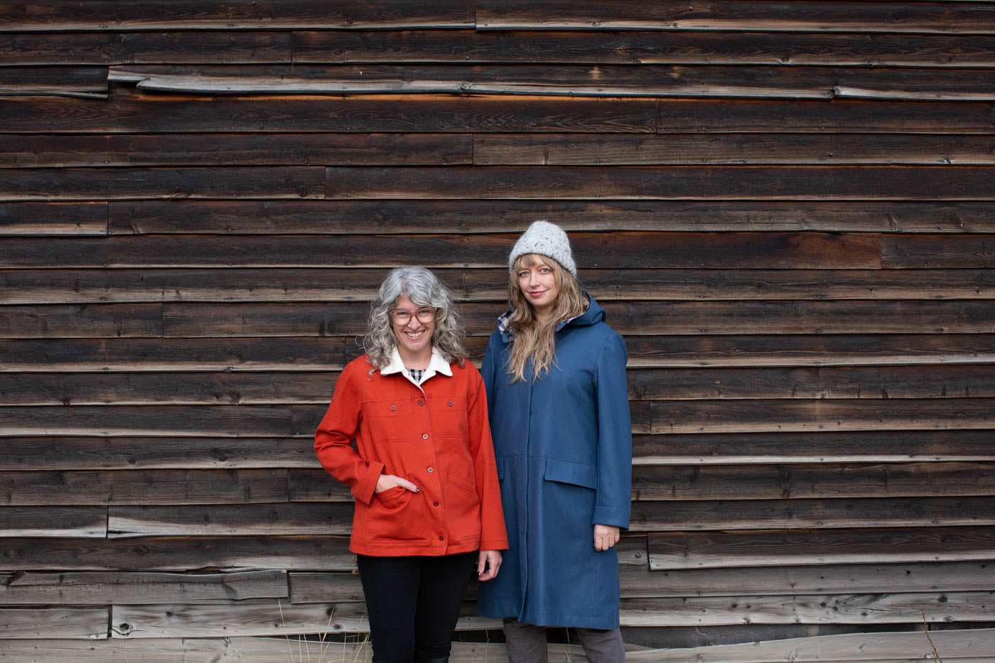 Amber and Jaime stand together outside against a weathered barnwood wall. Jaime wears her vibrant red Thayer Jacket with cream fleece lining showing at the collar. Amber wears her blue wool Hoodie Parka with a hand knit grey hat.