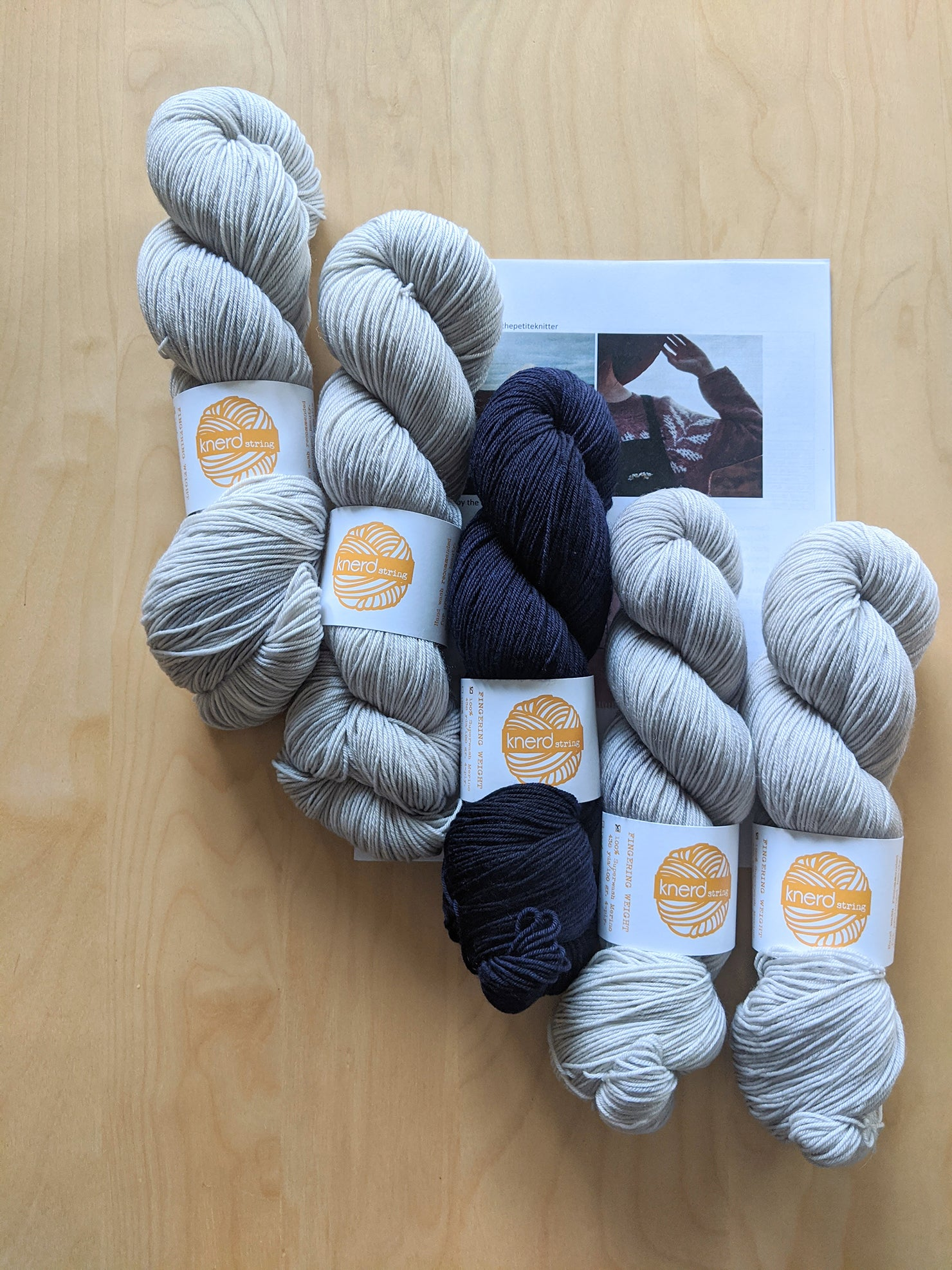 This is an image of the Knerd String supermerino yarn and the pattern on a table.