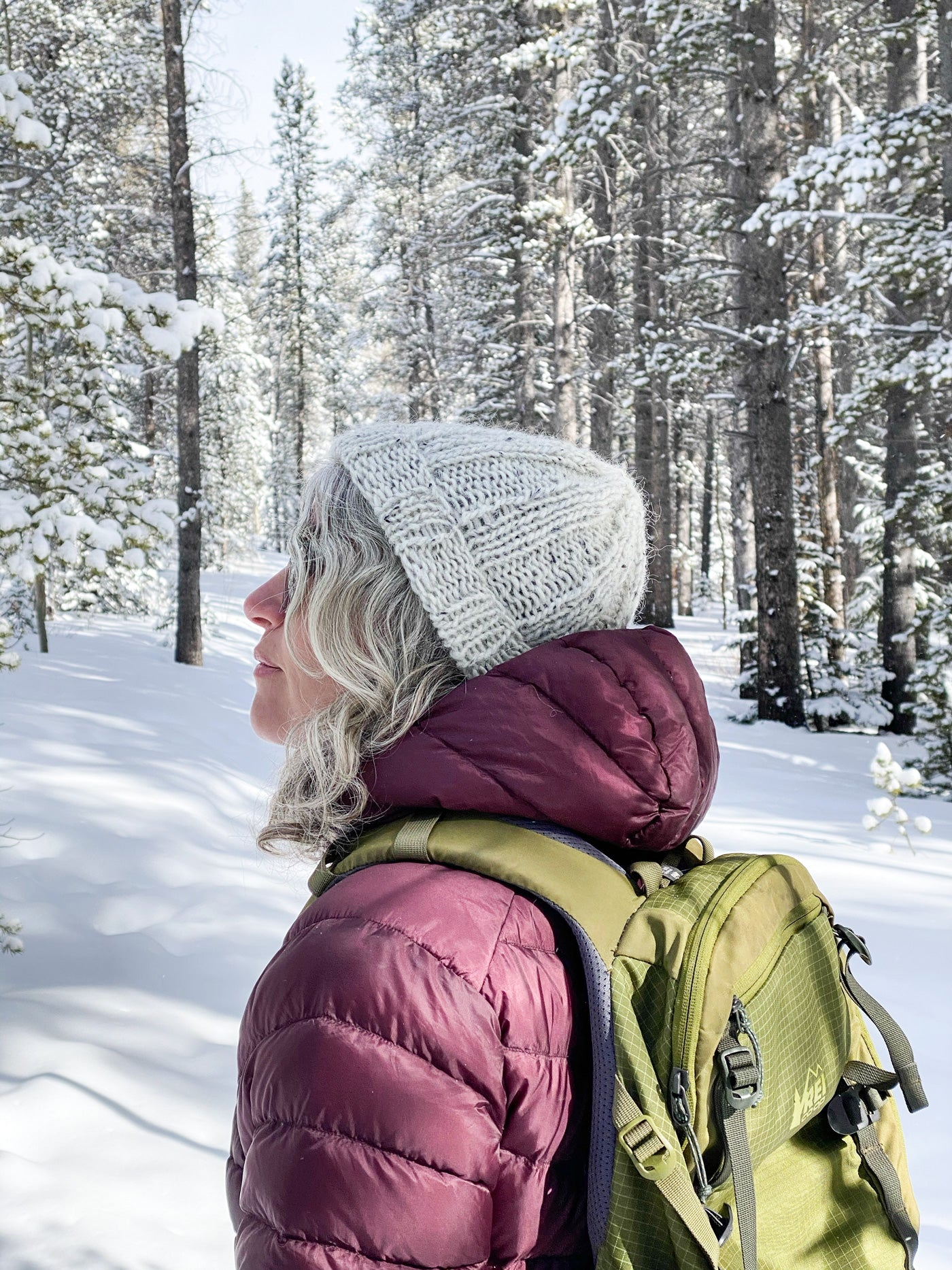 Jaime wears a pale grey, tweedy ribbed hat. She stands in a snowy forest of tall evergreens, keeping warm in a burgundy puffy jacket and olive hiking pack.