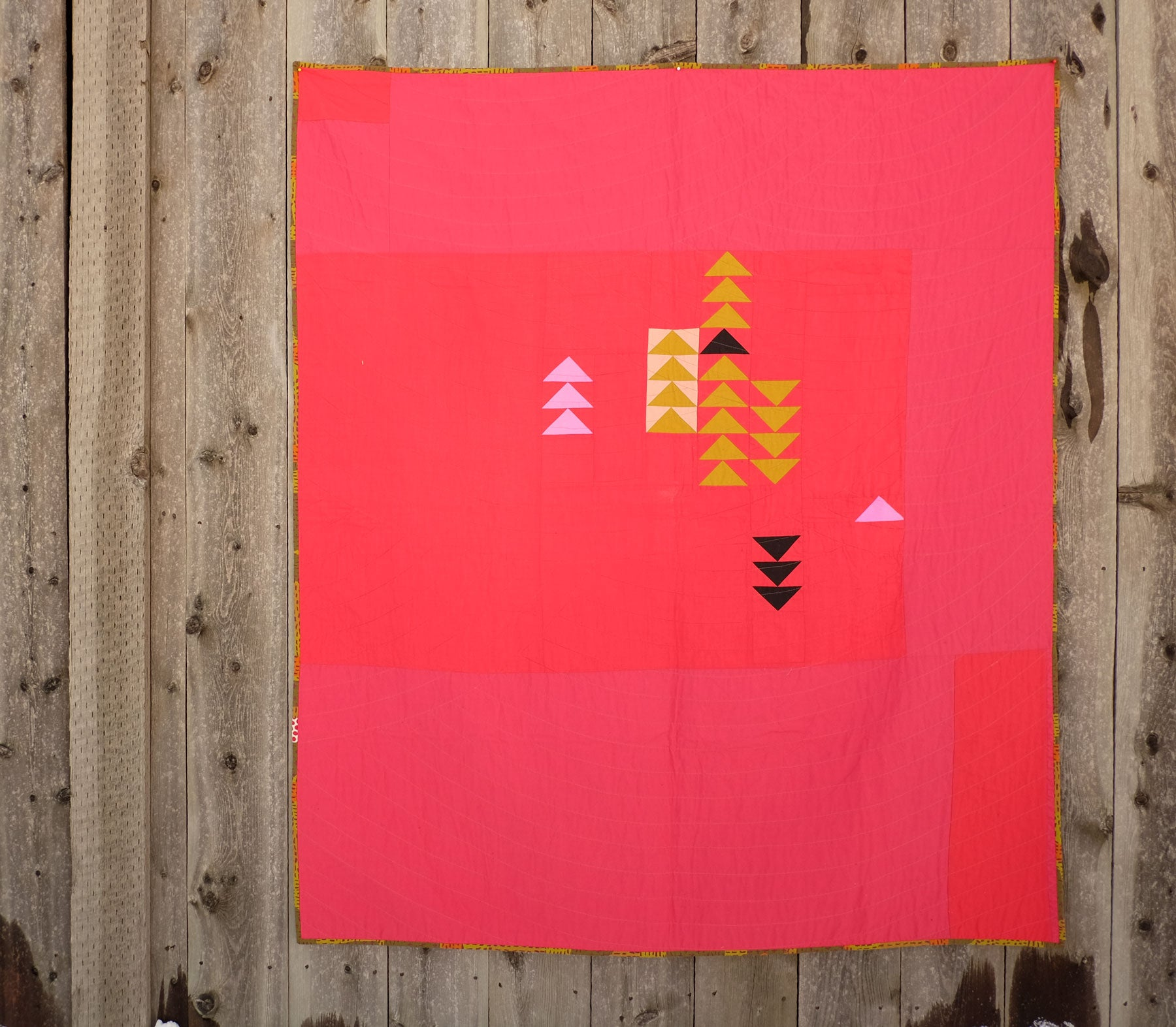 Shawna Doering's Red Hot Quilt hanging on a fence
