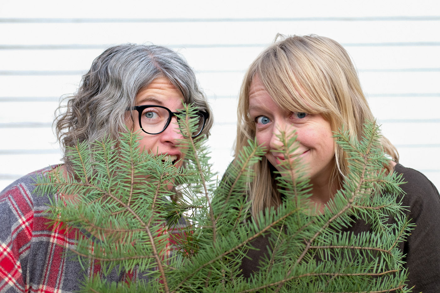 Jaime and Amber peeking out from some greenery